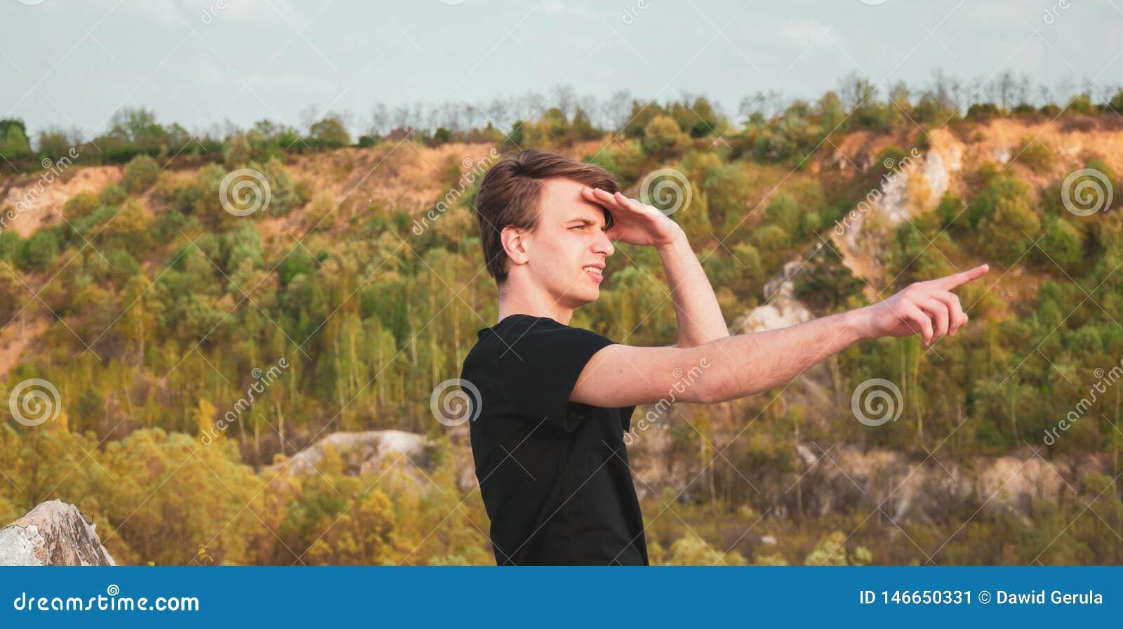 Młody człowiek wskazuje kierunek z jego palcem podczas gdy wycieczkujący w górach, horyzontalna fotografia
