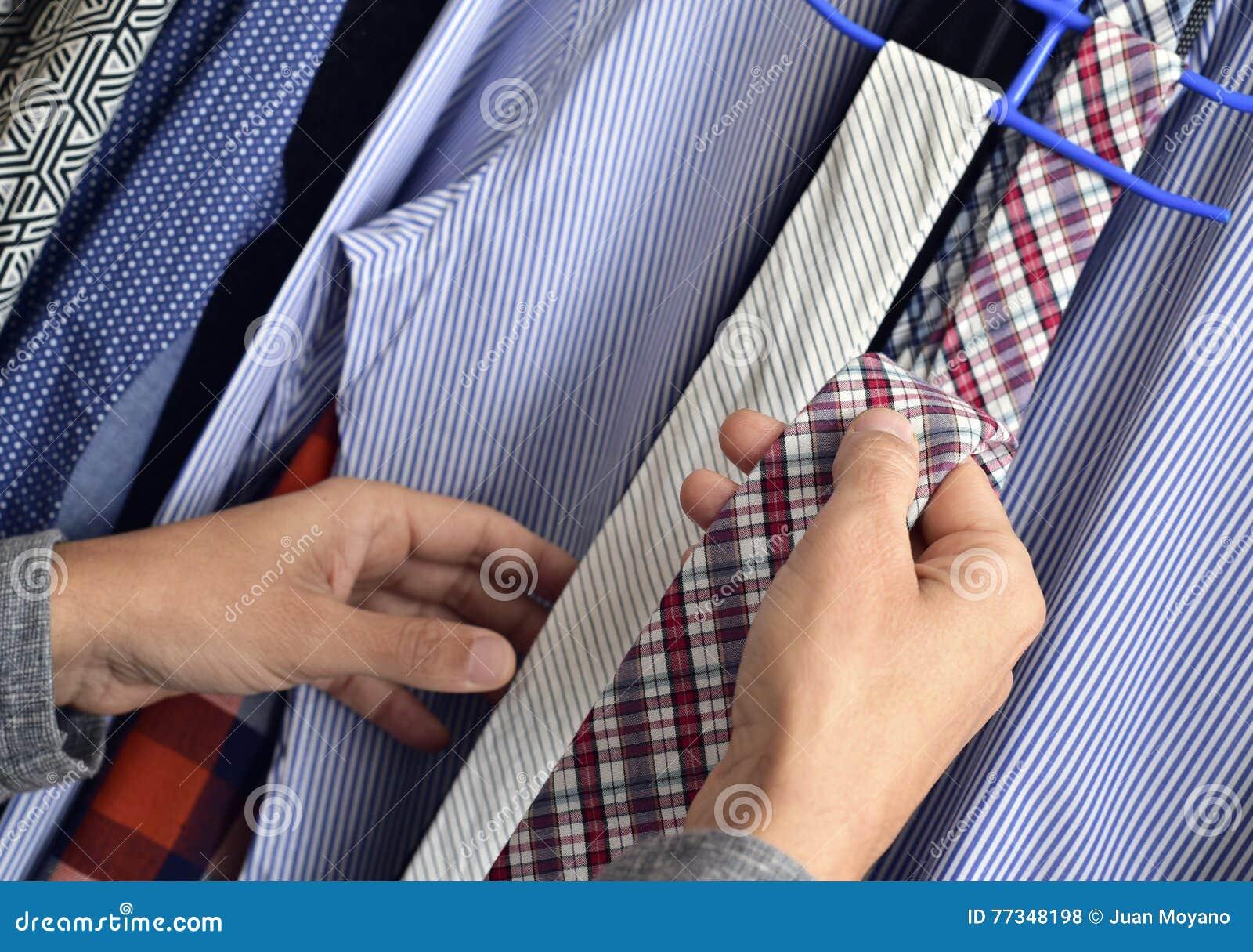 Młody człowiek wybiera krawat od szafy