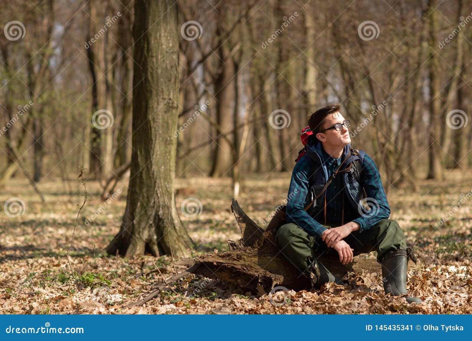 Młody człowiek wycieczkuje w lasowej naturze z plecakiem fizycznego ćwiczenia pojęciu i