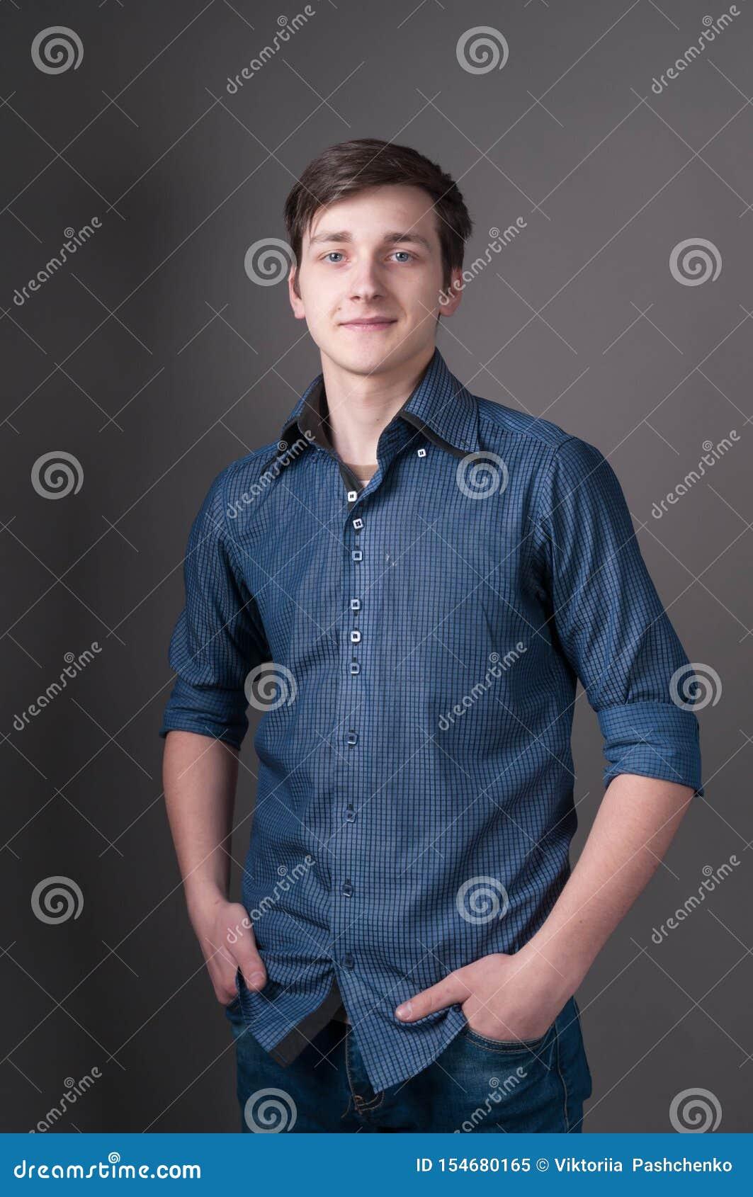 Młody człowiek z ciemnego włosy pozycją z rękami w kieszeniach