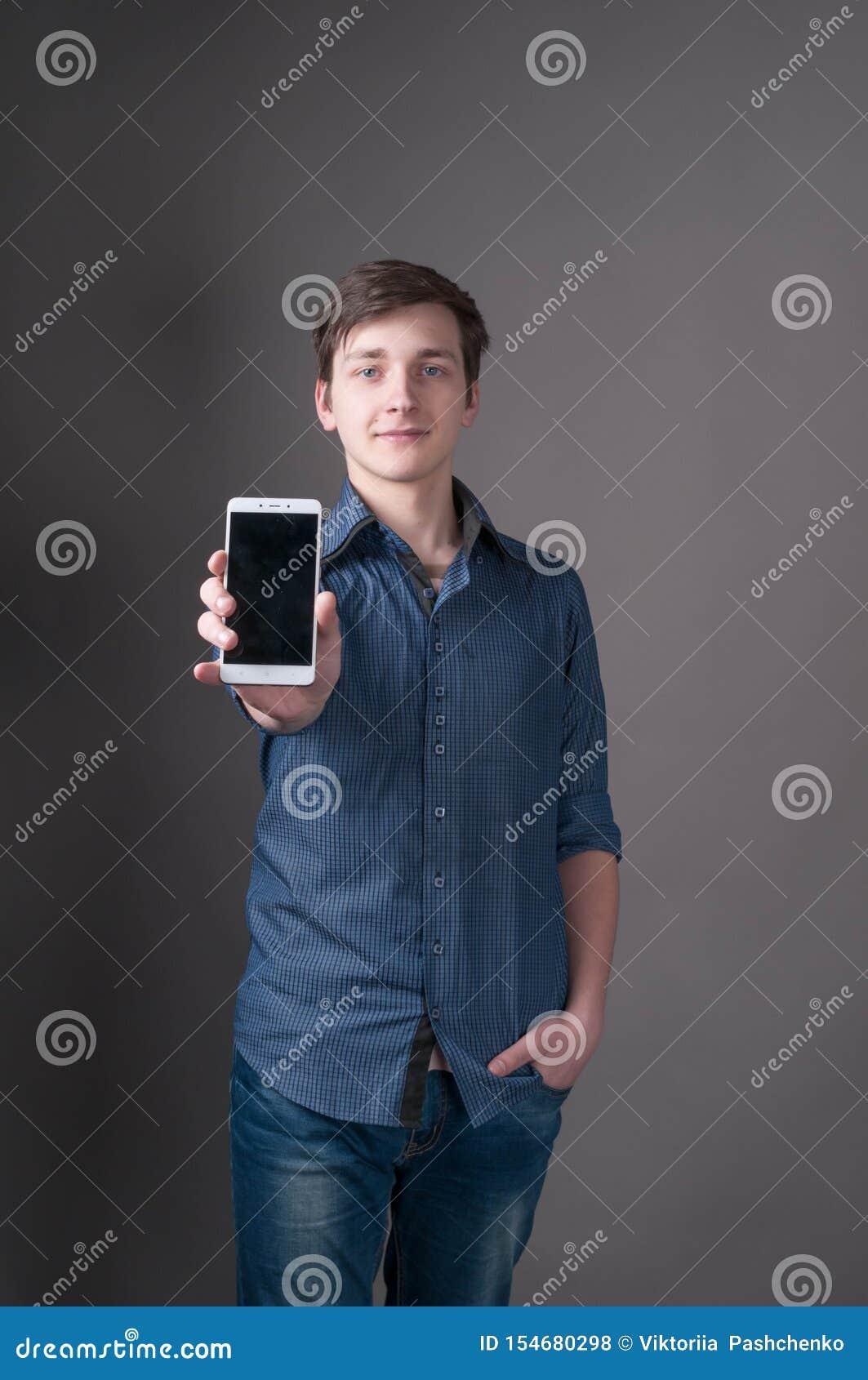 Młody człowiek z ciemnym włosy w błękitnej koszula, trzymający rękę w kieszeni, pokazuje smartphone z pustym ekranem