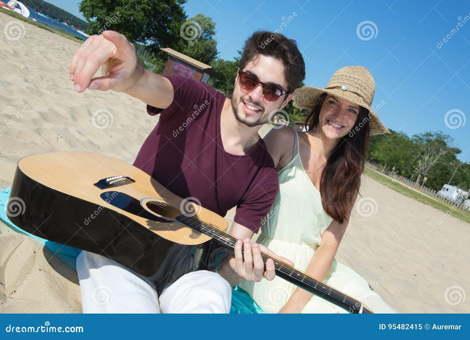 Młody człowiek z gitarą i dziewczyną na plaży