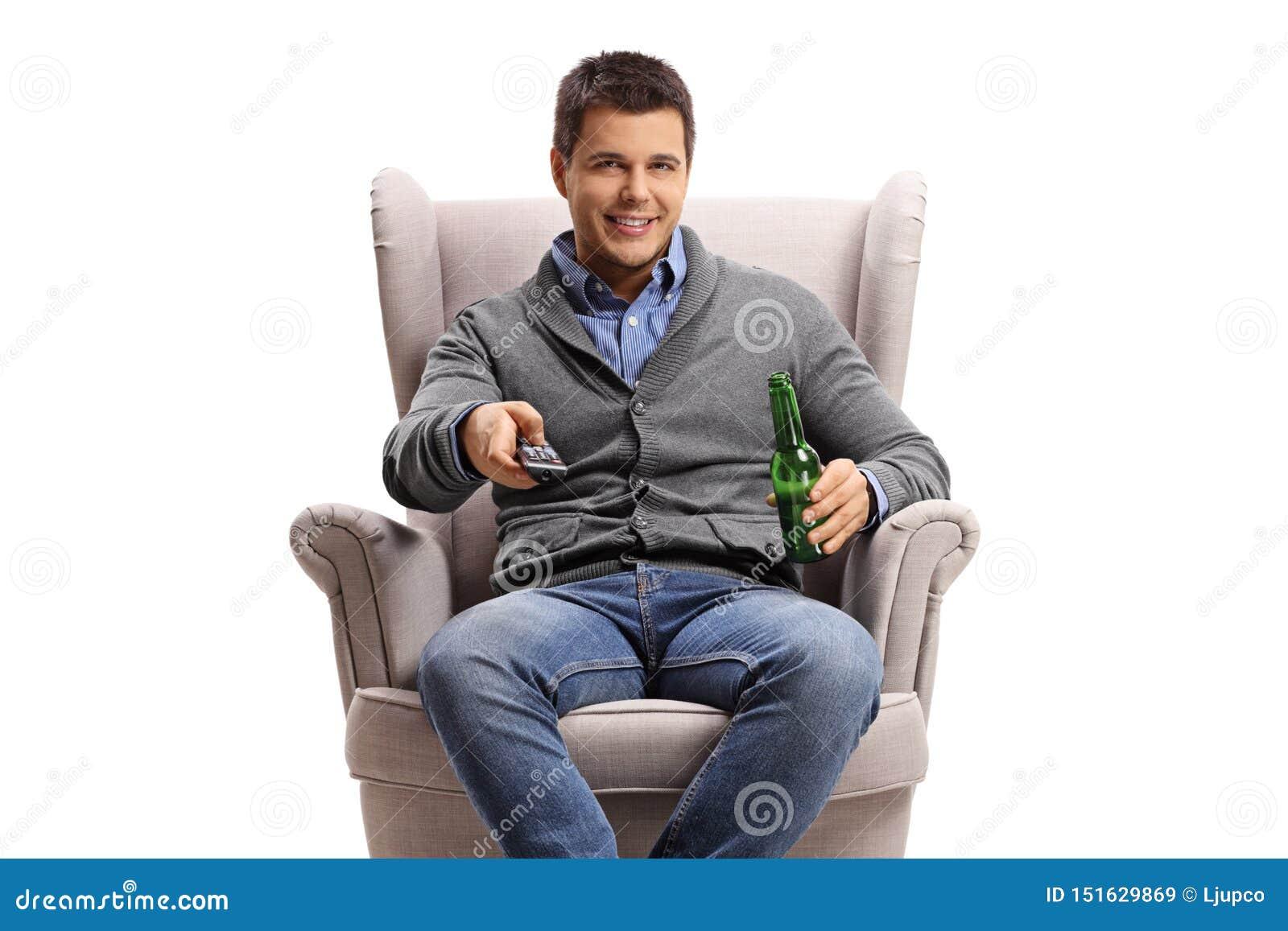 Młody człowiek z pilotem do tv i piwną butelką w karle