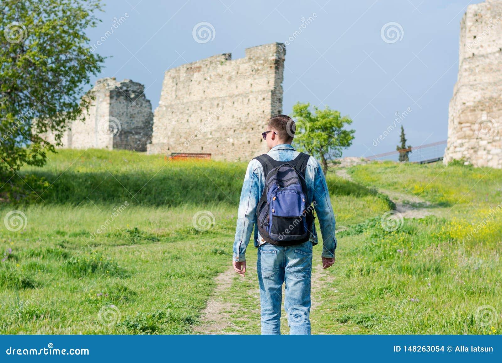 Młody człowiek z plecakiem, turysta, iść wzdłuż ścieżki Trigonion wierza w Górnym Grodzkim fortecy w Saloniki,