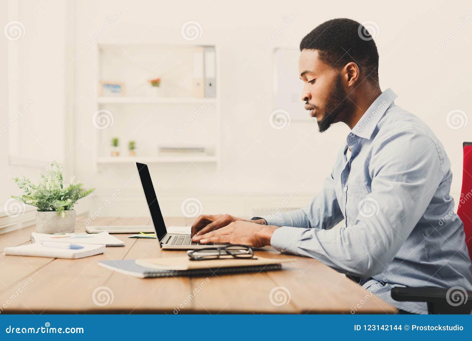 Młody czarny biznesmen pracuje z laptopem