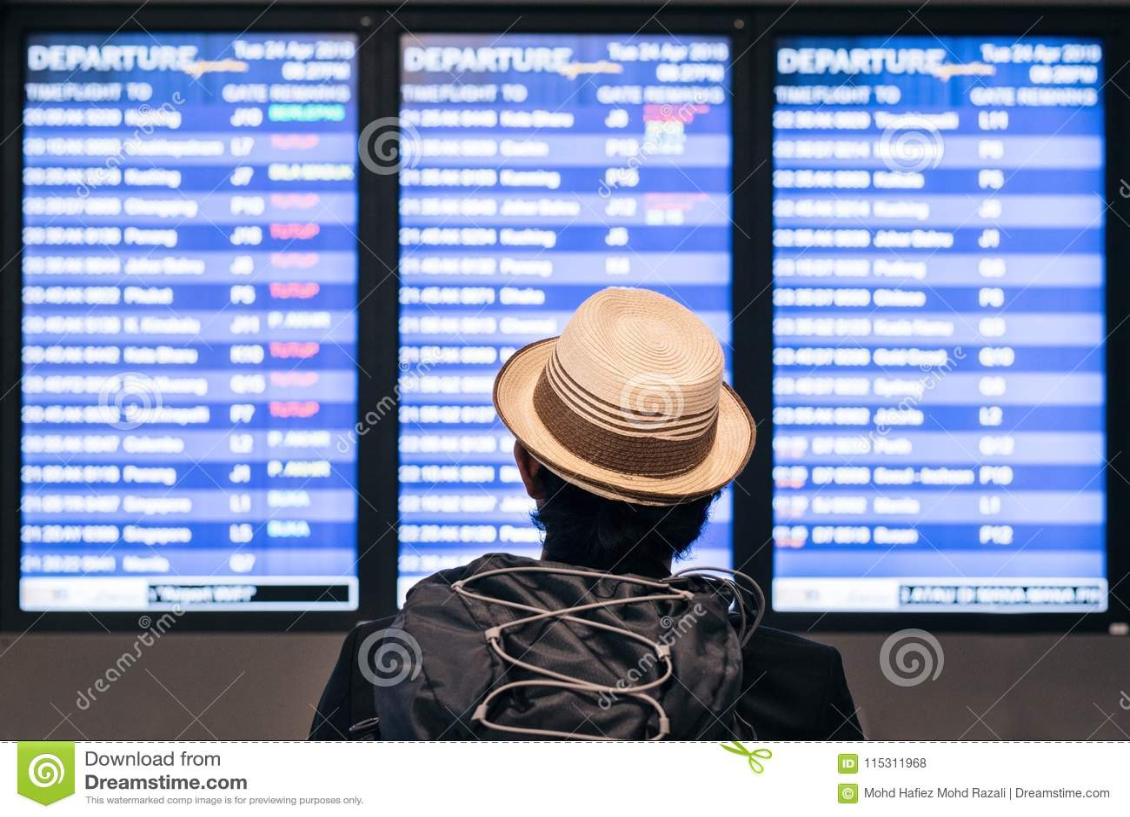 Młody dorosły turystyczny podróżnika backpaker patrzeje lotniskowego lota rozkładu rozkład zajęć na ekranie