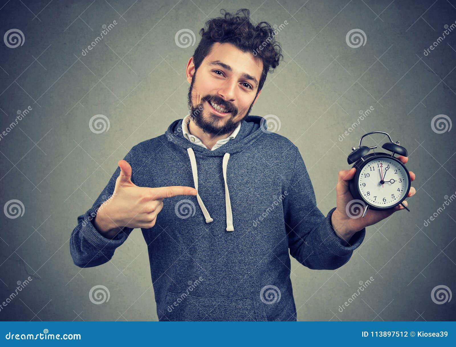 Młody ekspresyjny szczęśliwy modnisia mężczyzna mienia budzik