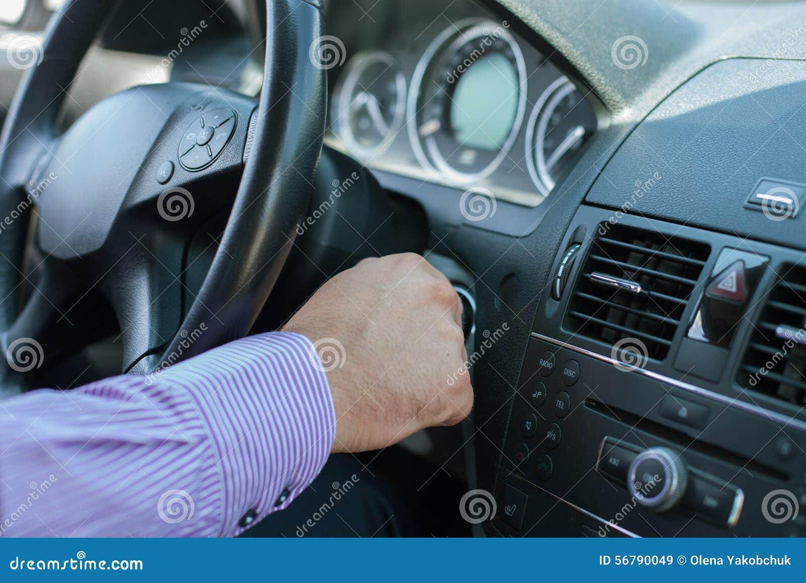 Młody elegancki mężczyzna zaczyna jego samochód