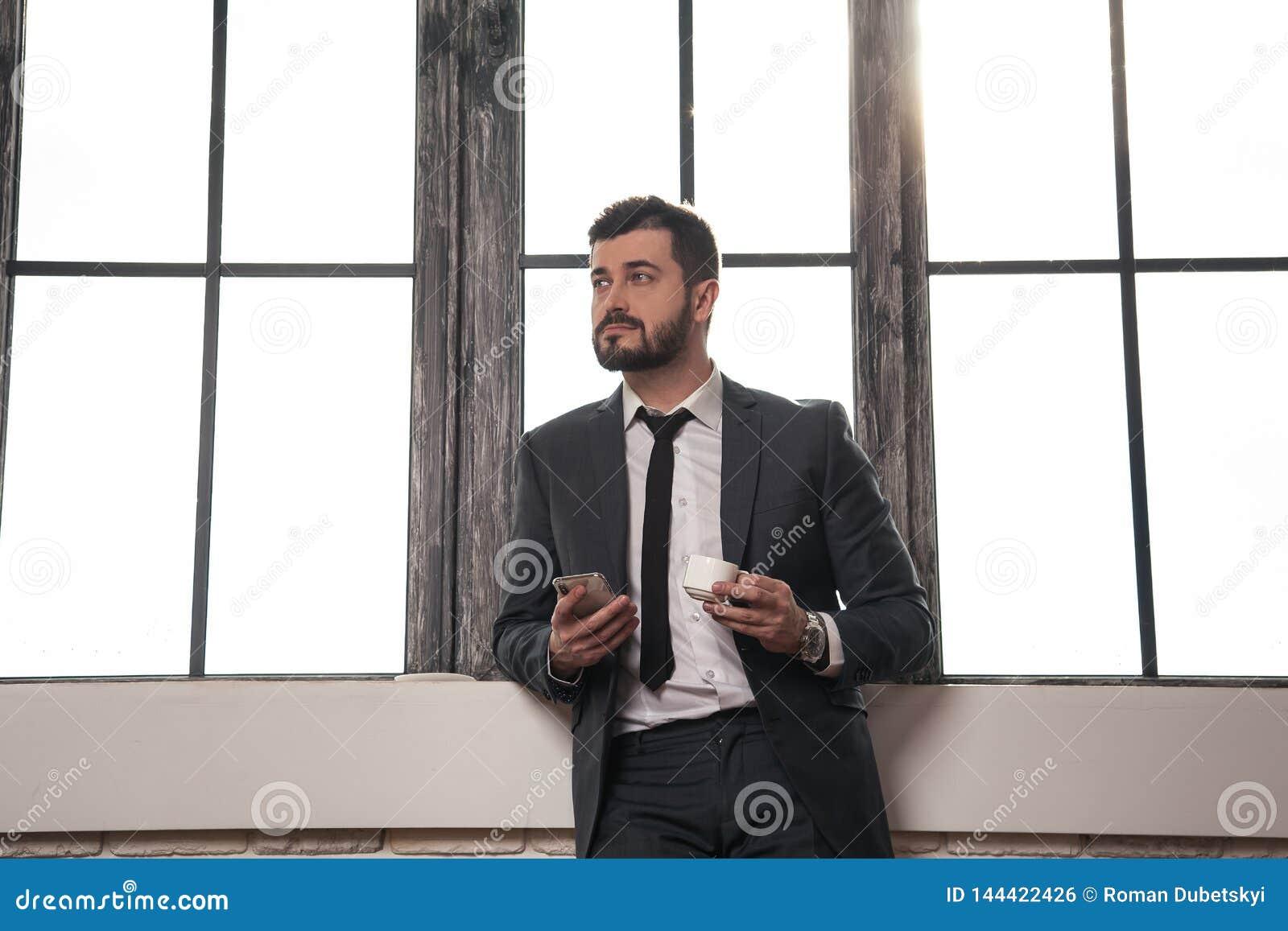 Młody elegancki przystojny biznesmen stoi bezczynnie okno przy jego biurem ma kawową przerwę i trzyma telefon komórkowego w jego