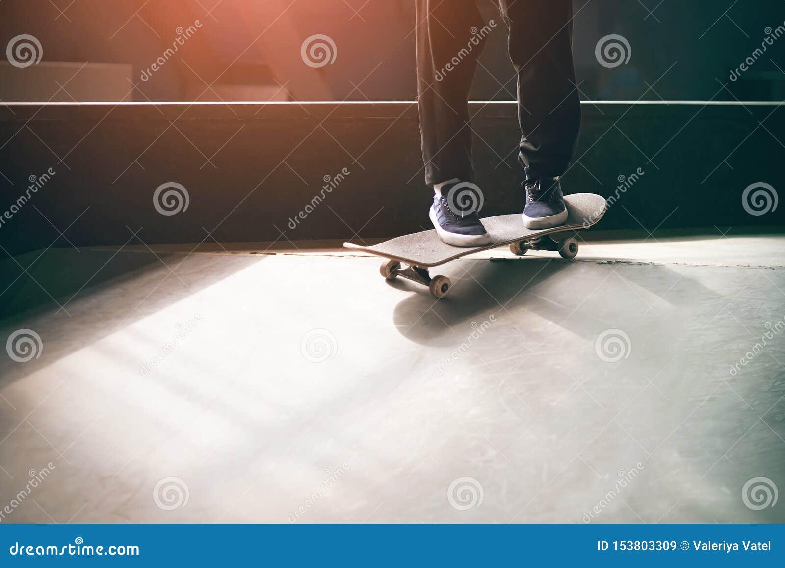 Młody facet w błękitnych sneakers jedzie deskorolka na rampie