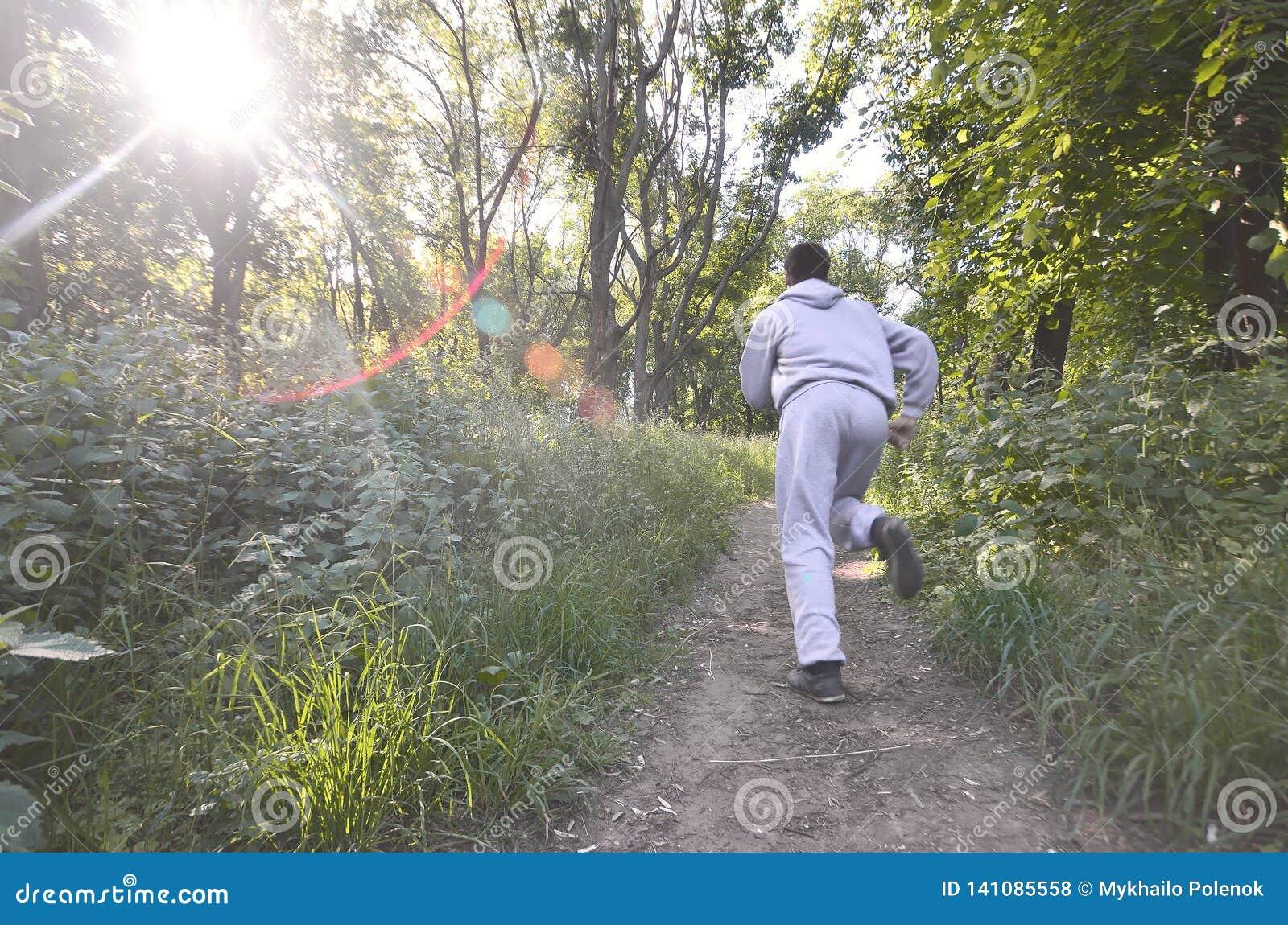 Młody facet w szarości bawi się kostiumów bieg wzdłuż ścieżki wśród
