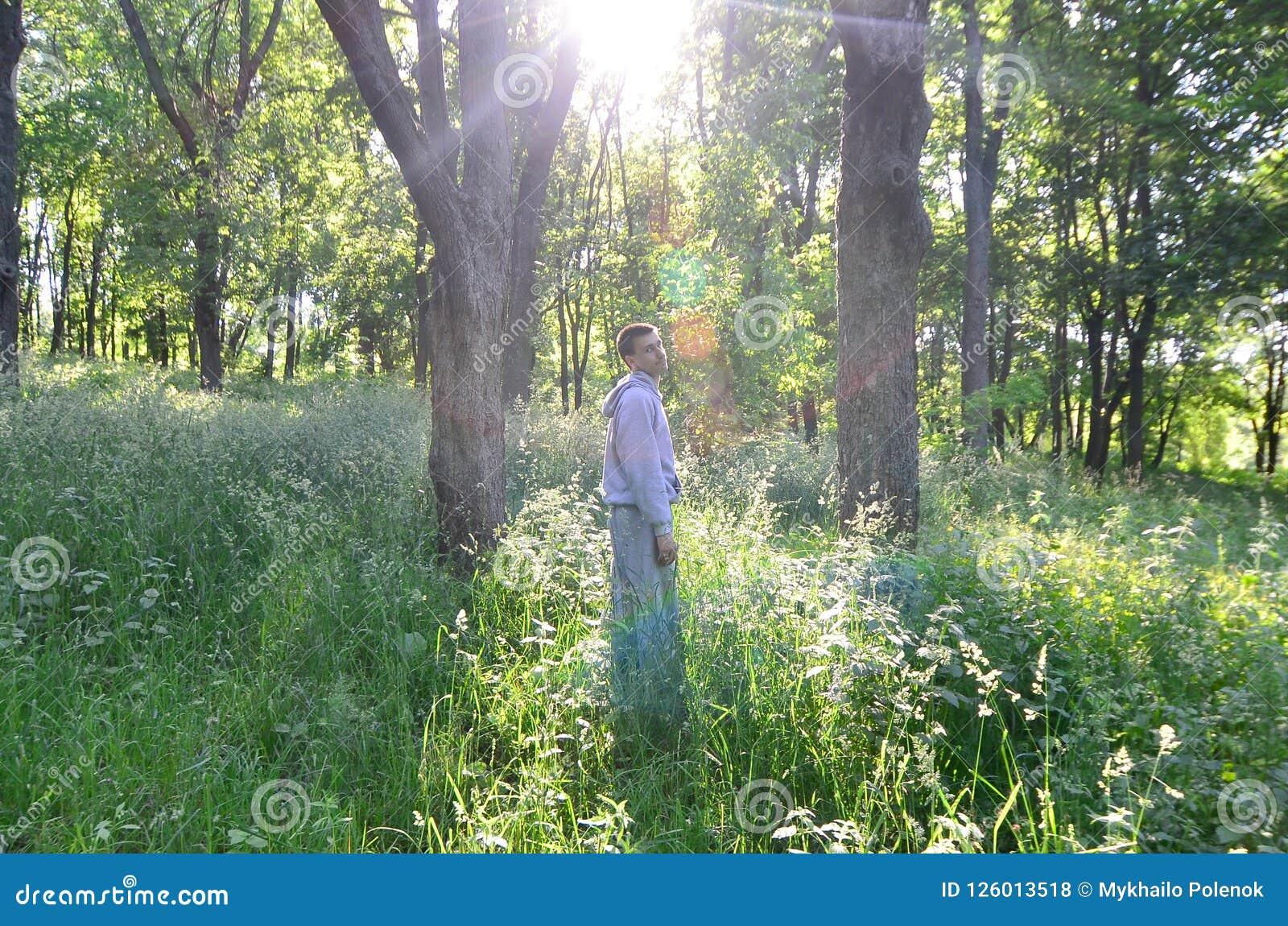 Młody facet w szarości bawi się kostiumów stojaki naprzeciw słońca wśród