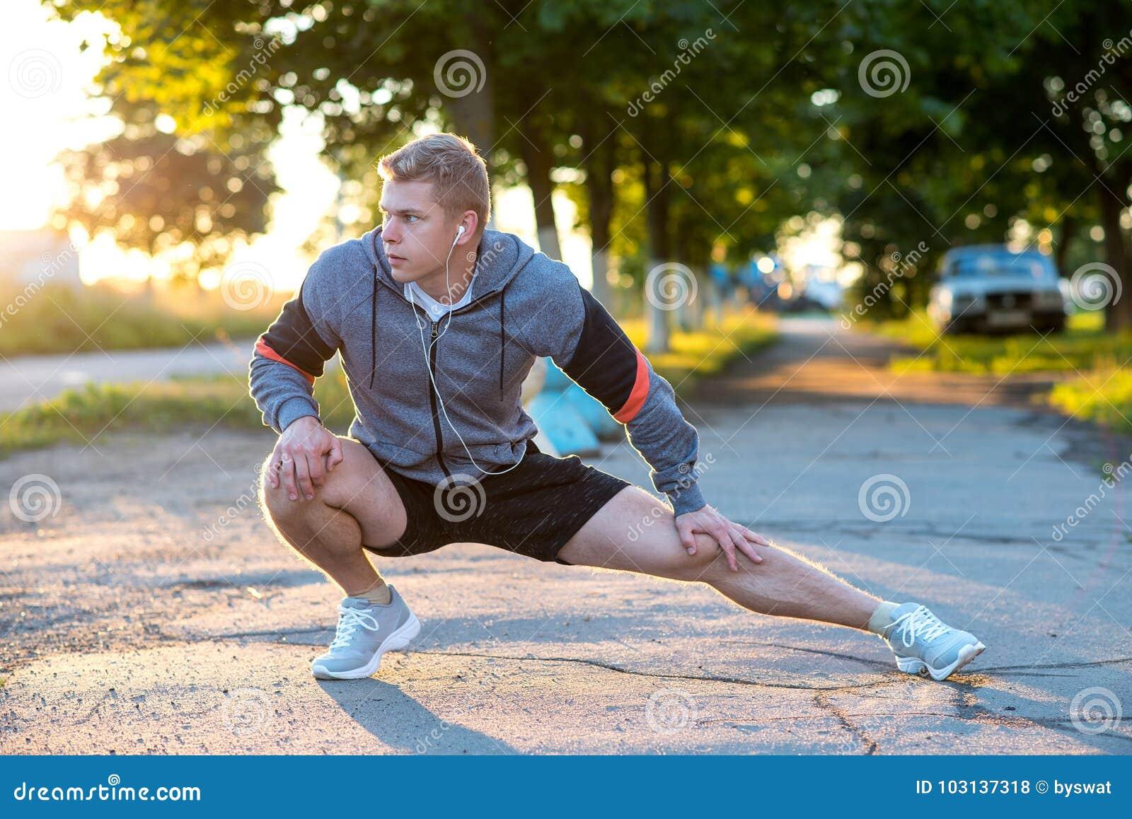 Młody faceta biegacz w wczesnym poranku robi gimnastykom jego cieki w hełmofonach Rozgrzewka złącza