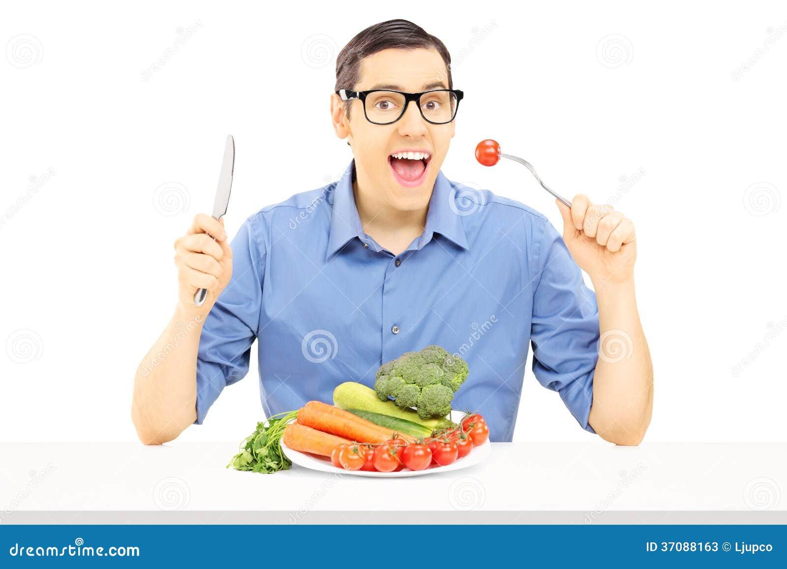 Download Młody Faceta Obsiadanie Przy Stołowymi łasowań Warzywami Obraz Stock - Obraz złożonej z odosobniony, pieprz: 37088163