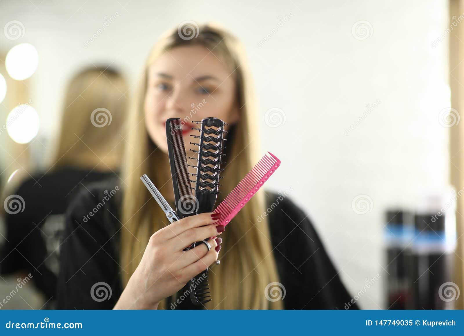 Młody fryzjera chwyta Hairbrush i nożyce