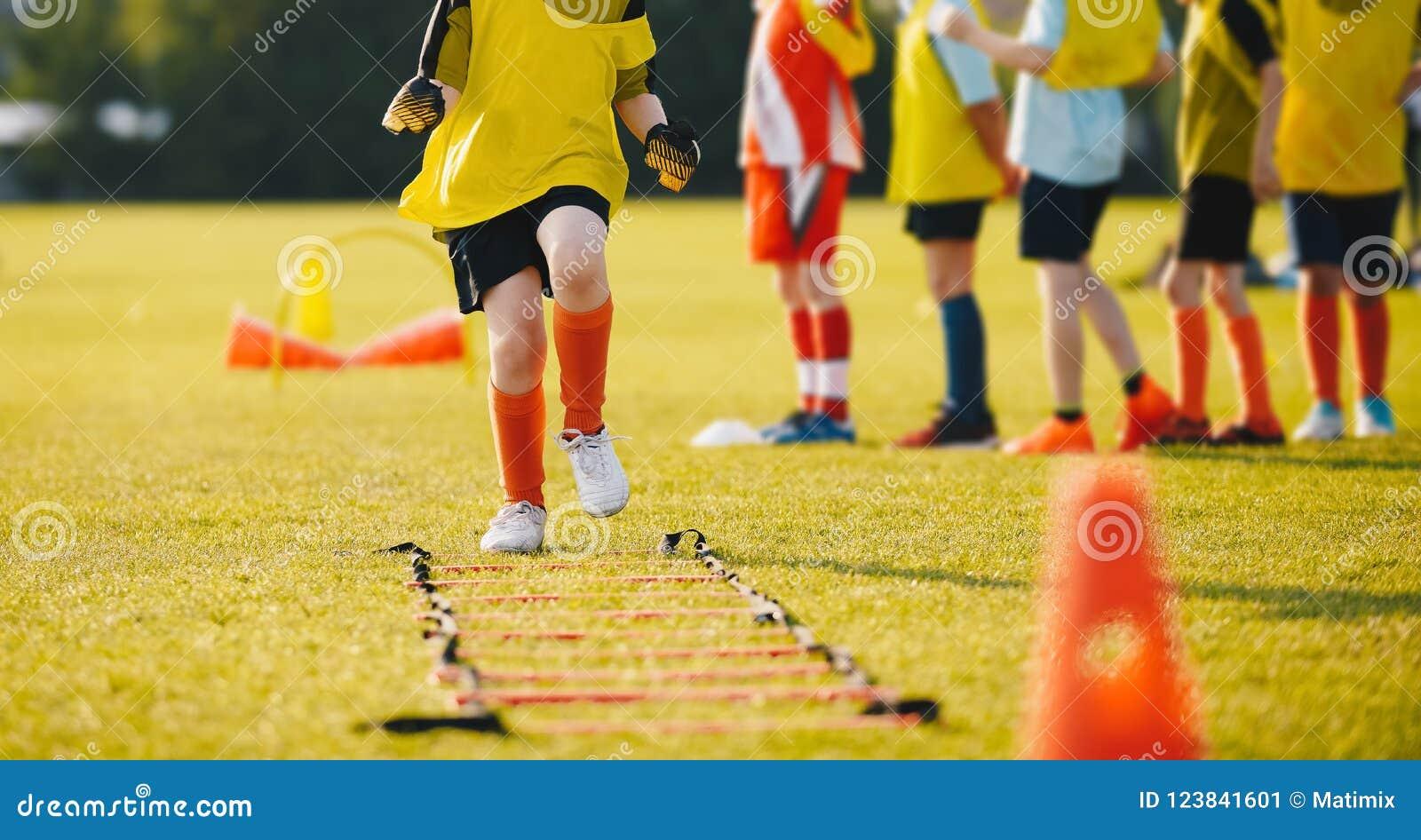 Młody futbolista w Żółtym Sportswear przy sesją szkoleniowa na trawy boisko do piłki nożnej
