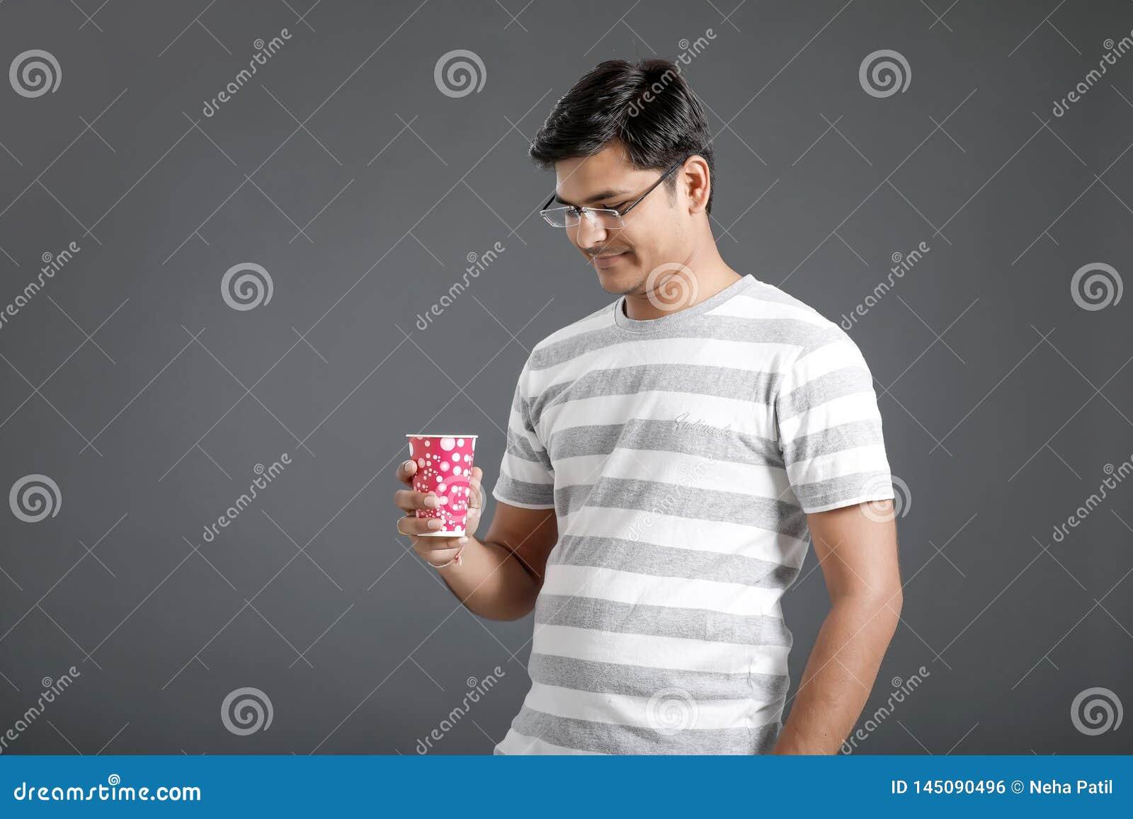 Młody indyjski mężczyzna pije wodę