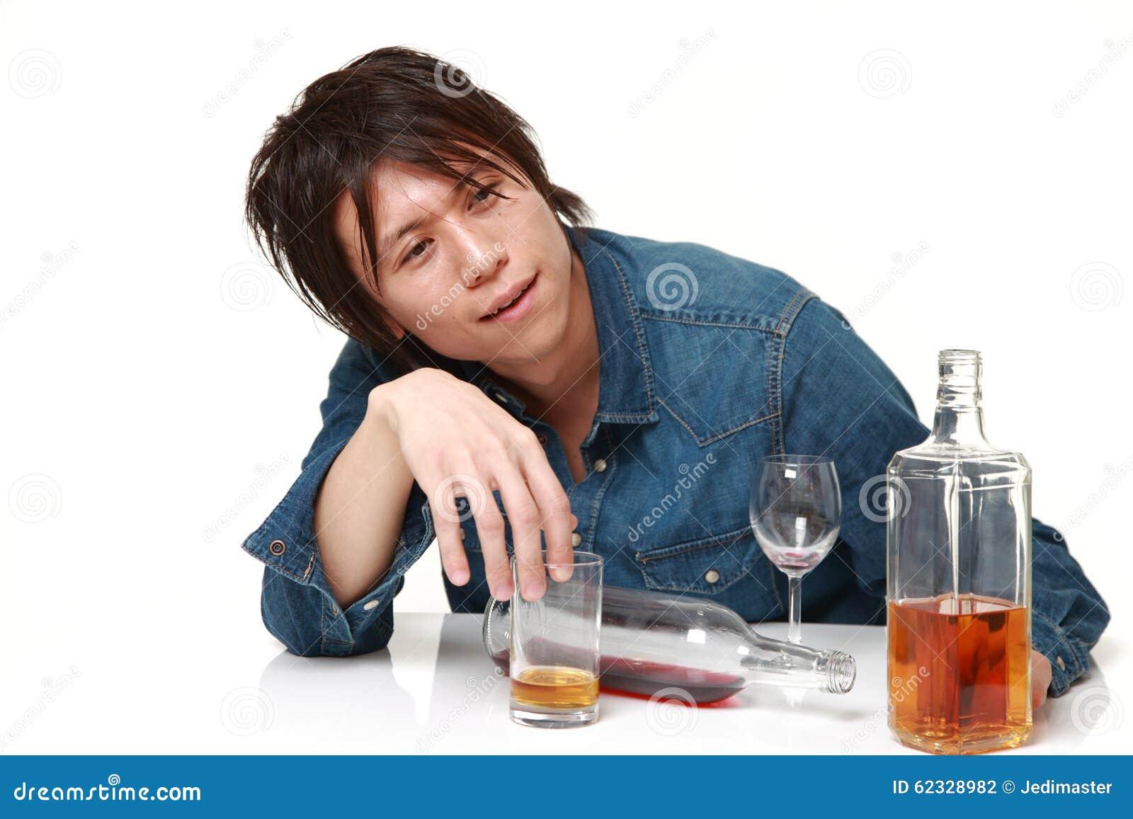 Młody Japoński mężczyzna pijący zbyt dużo