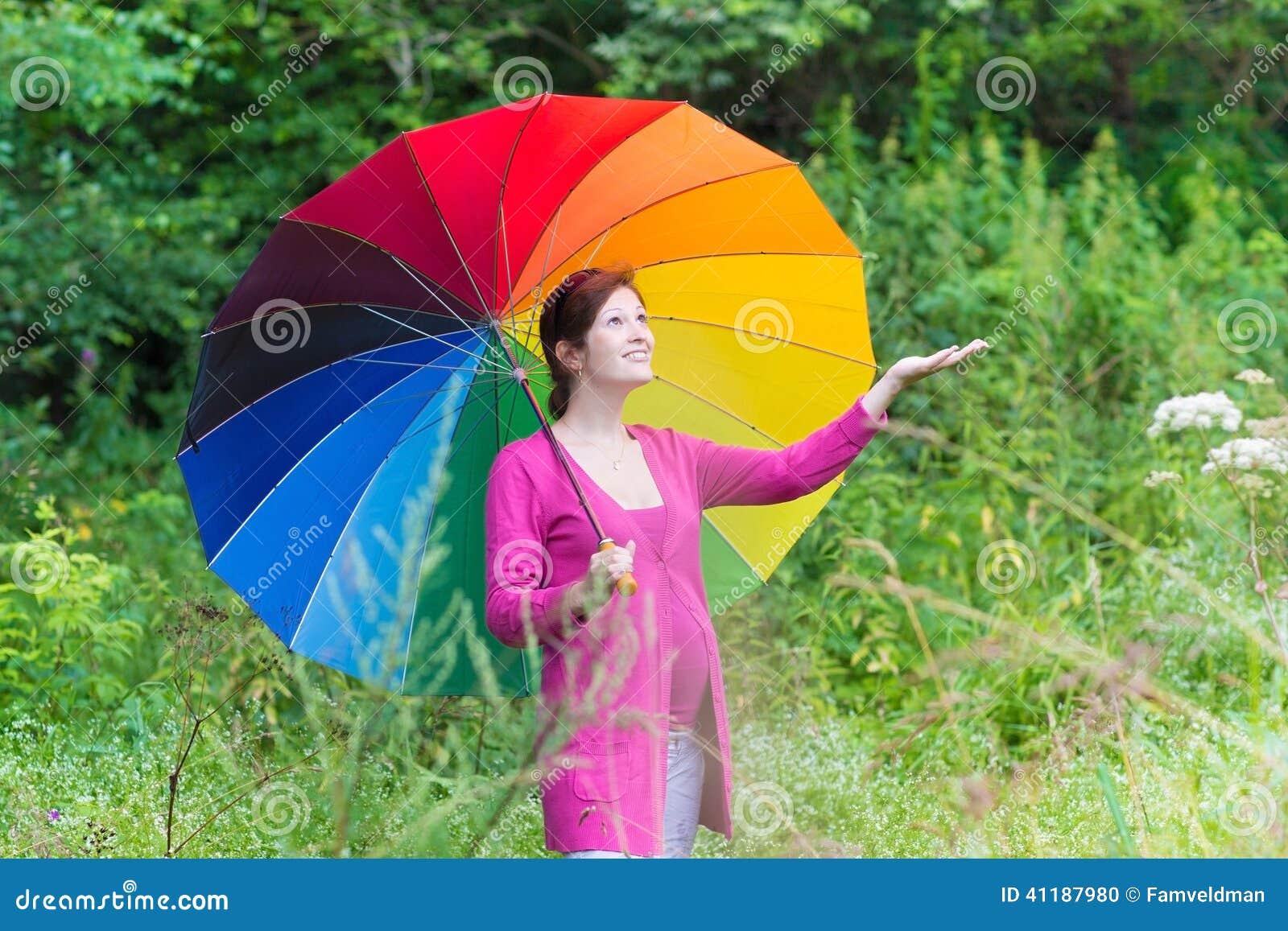 Młody kobieta w ciąży odprowadzenie pod kolorowym parasolem