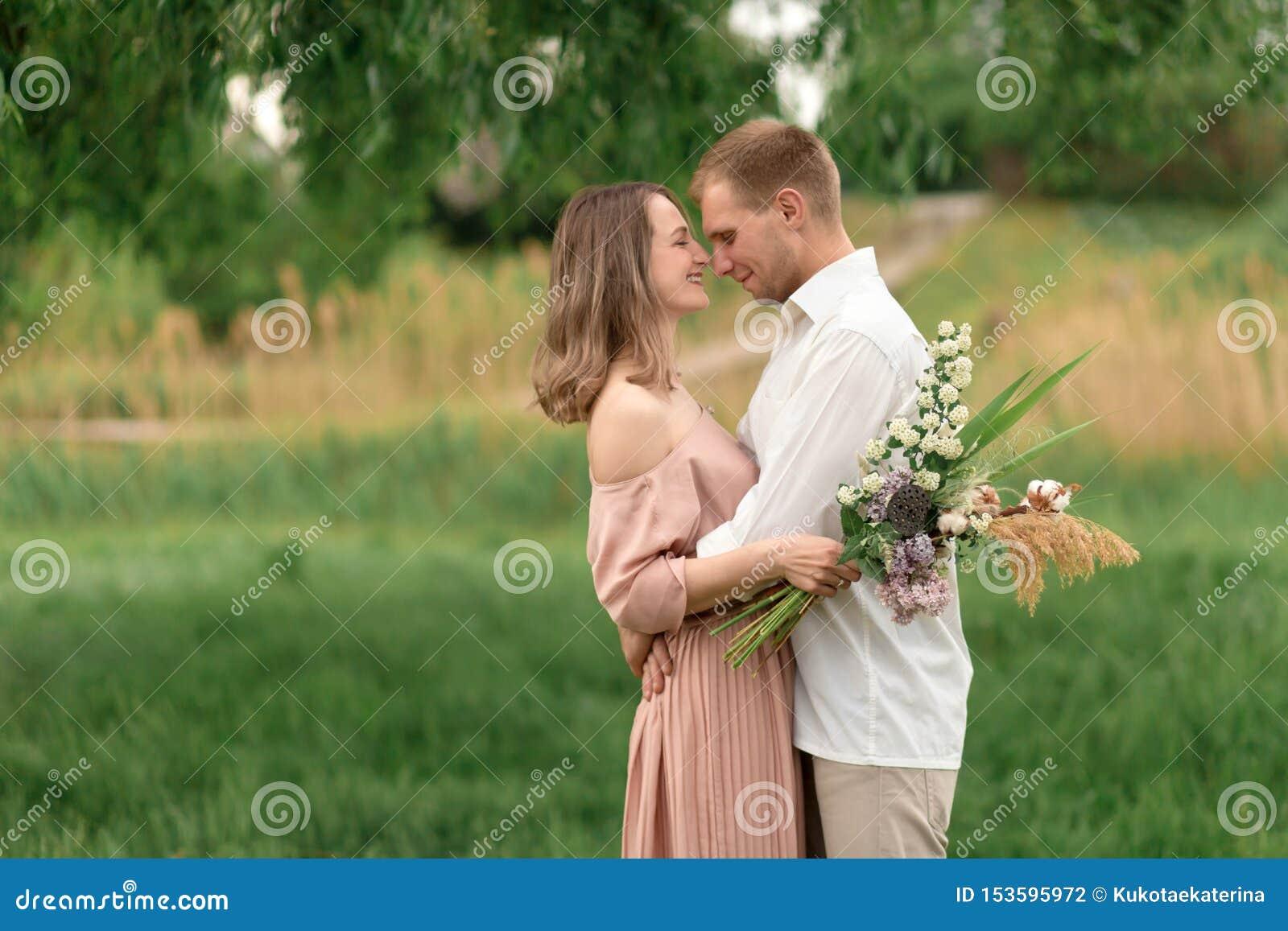 Młody kochający pary przytulenie, taniec na zielonej trawie na gazonie i Piękny i szczęśliwy dotyk kobiety i mężczyzny delikatnie