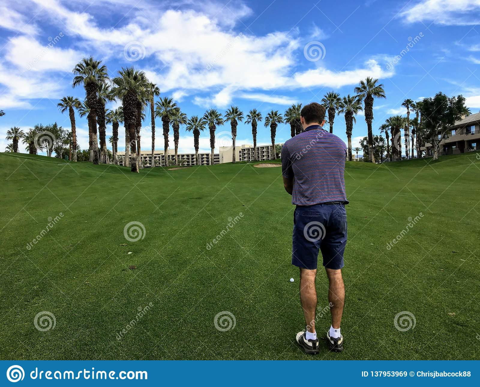 Młody męski golfista uszeregowywa jego podejście strzelał od środka farwater na normie 4 na polu golfowym w palm springs