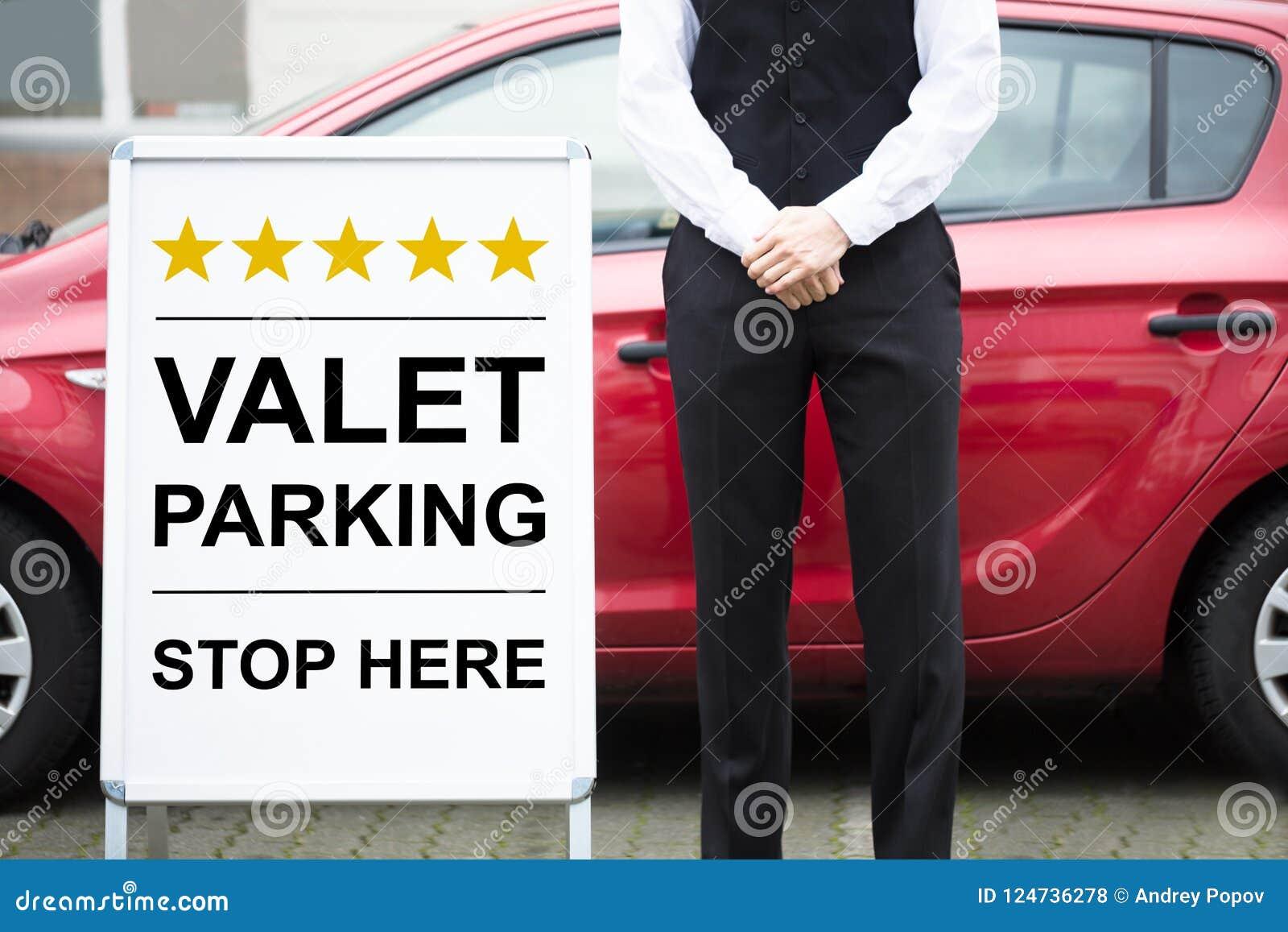 Młody Męski lokaj Stoi Blisko ostawianie samochodu na parking przez obsługę znaka
