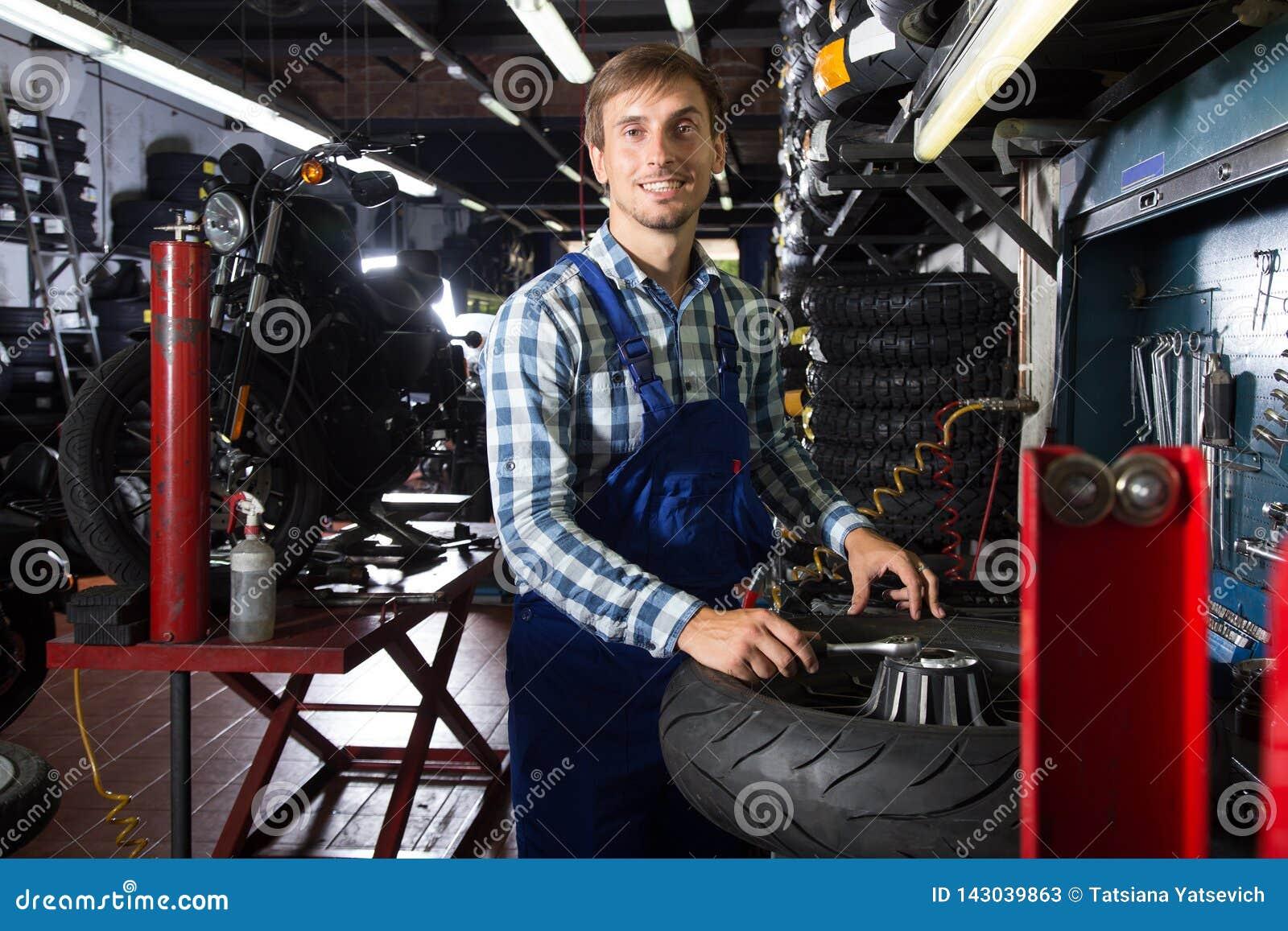 Młody męski mechanik pracuje w auto remontowym sklepie