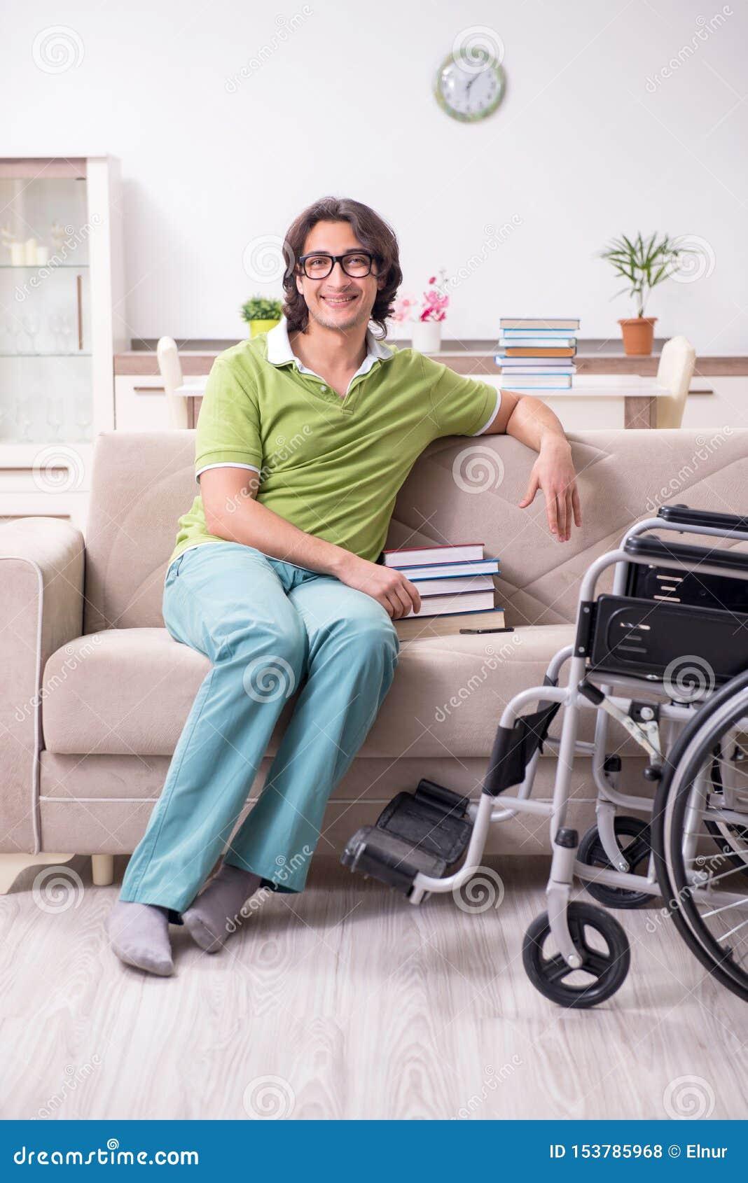 Młody męski uczeń w wózku inwalidzkim w domu