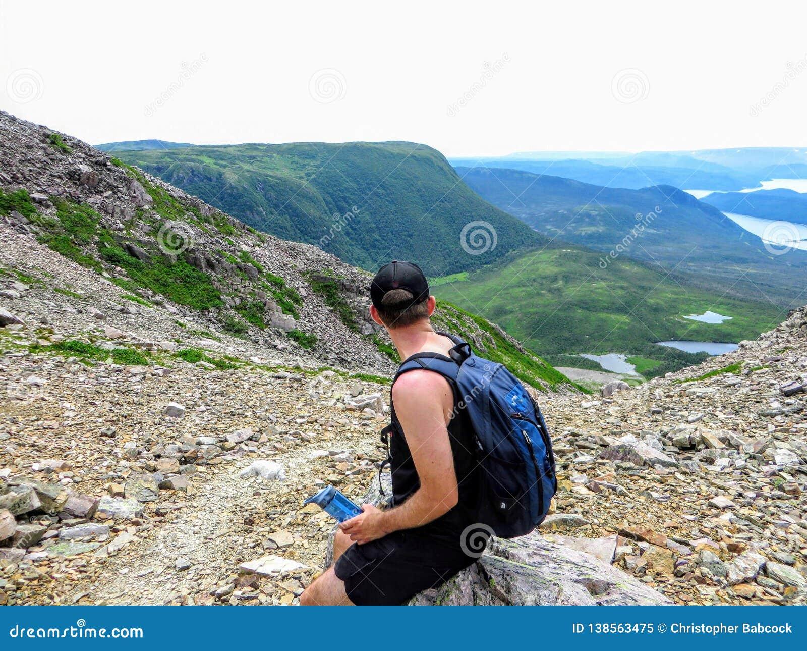 Młody męski wycieczkowicz podziwia spektakularny widoki na od Gros Morne góry w Gros Morne parku narodowym