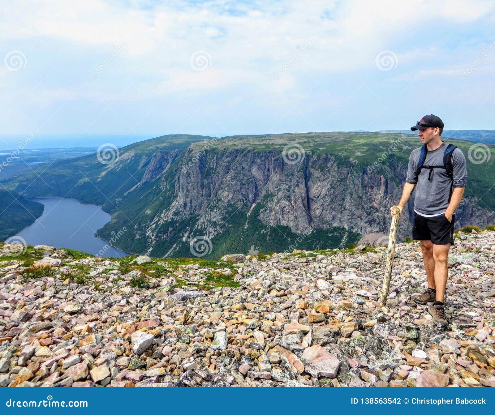 Młody męski wycieczkowicz podziwia spektakularny widoki na od Gros Morne góry w Gros Morne parku narodowym, wodołaz