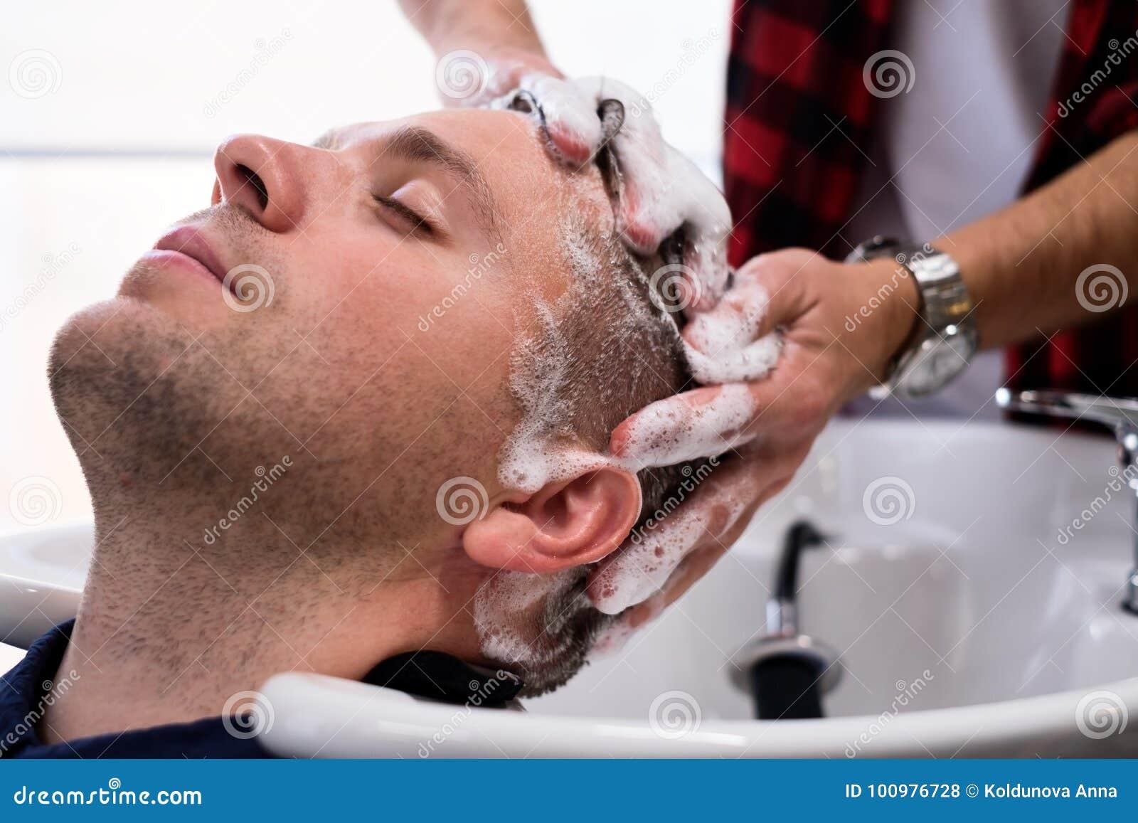 Młody Mcaucasian mężczyzna jest relaksujący W zakładzie fryzjerskim podczas ostrzyżenia