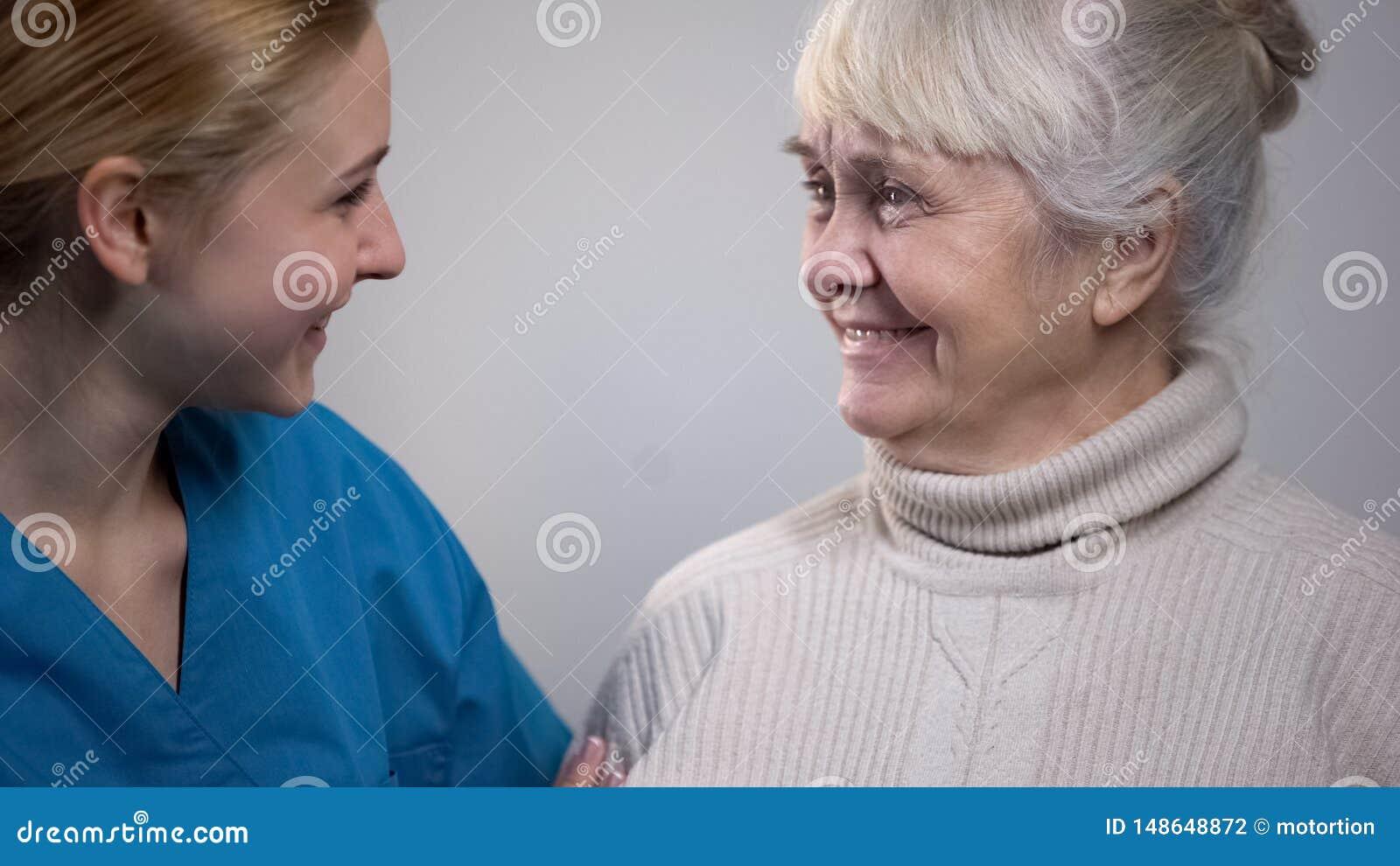 M?ody medyczny pracownik opowiada z u?miechni?t? starsz? dam? w szpitalu, dobre wie?ci