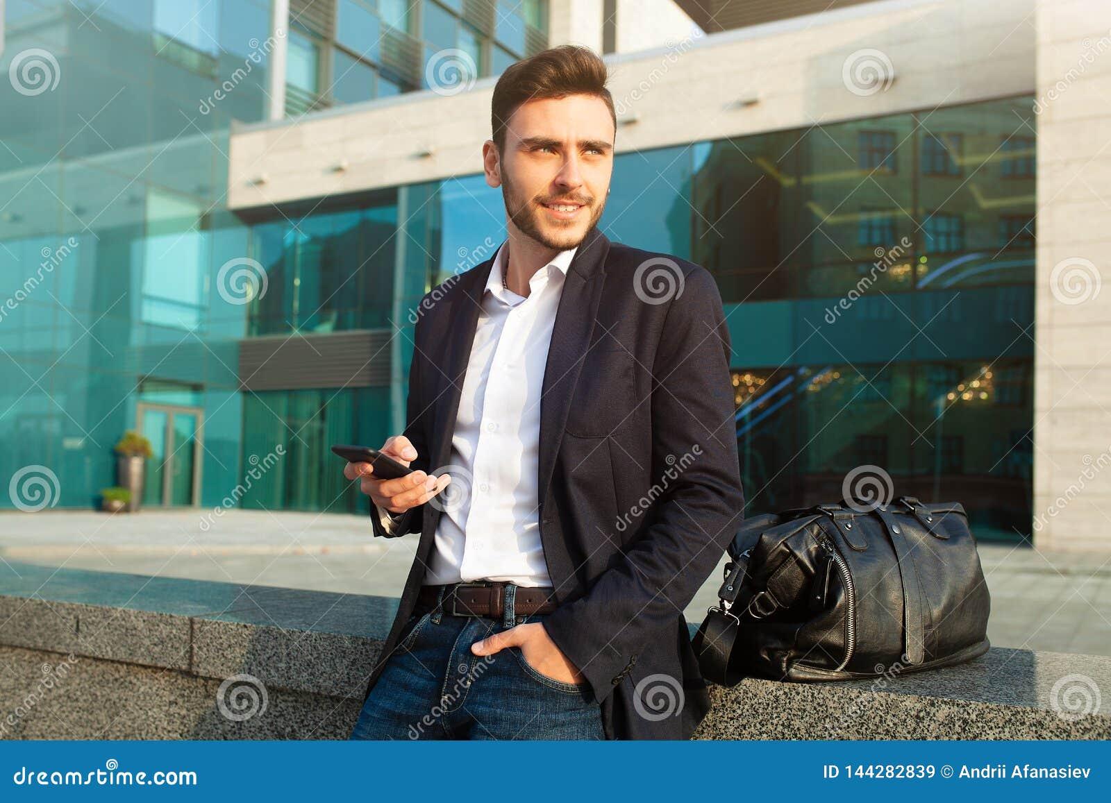 Młody miastowy fachowy mężczyzna używa mądrze telefon Biznesmena mienia mobilny smartphone używać app sms texting wiadomość jest