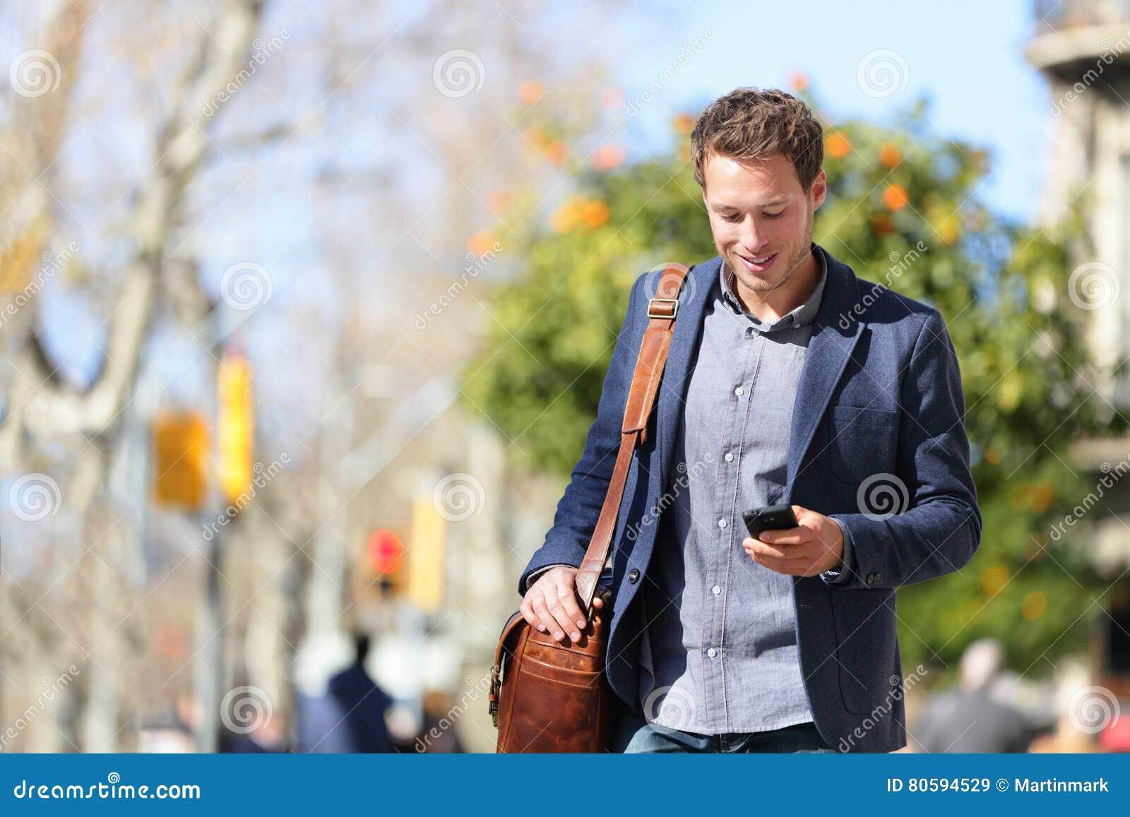 Młody miastowy fachowy mężczyzna używa smartphone app