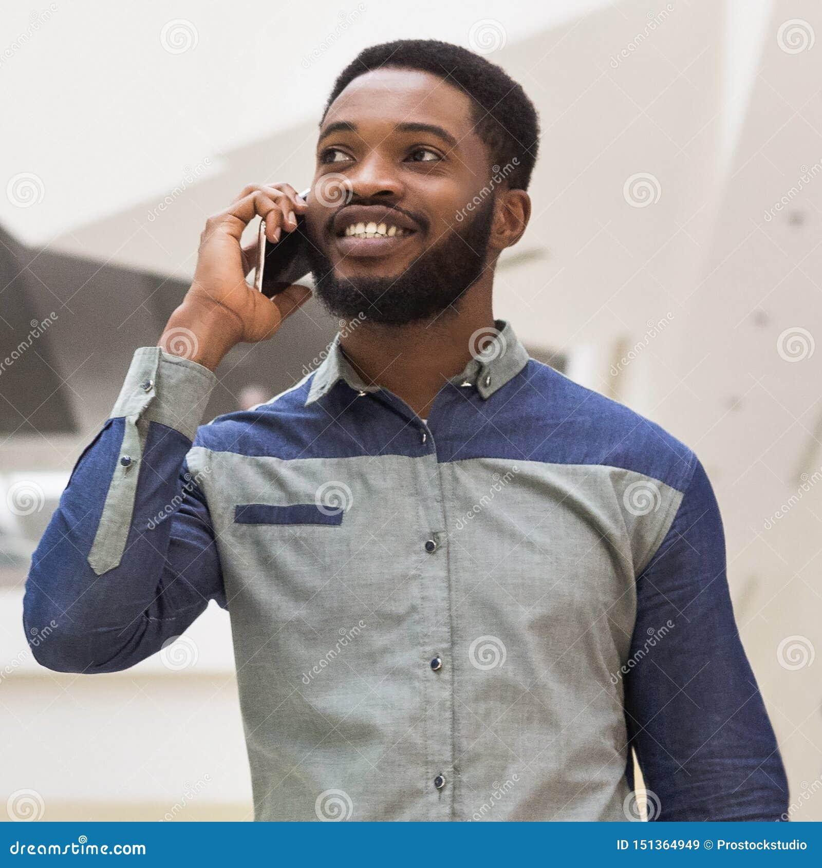Młody millennial afrykański mężczyzna opowiada na telefonie