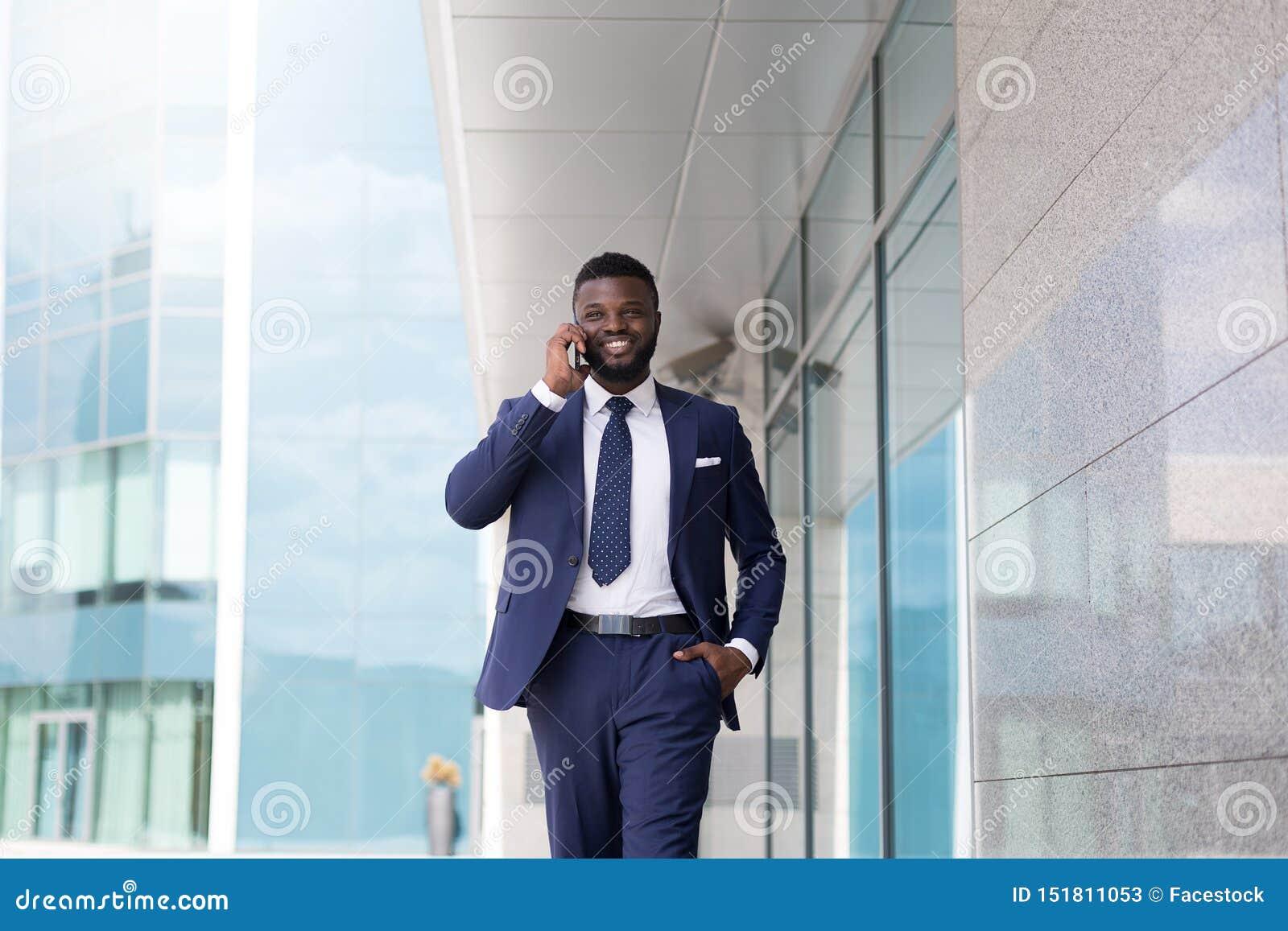Młody millennial CEO mówienie z nowym klientem na zewnątrz biura