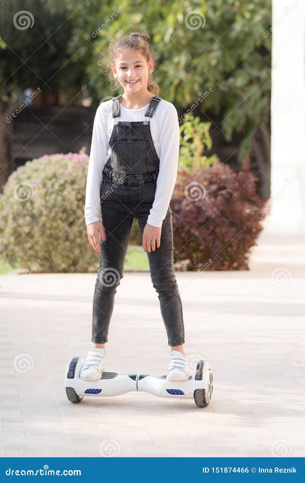 Młody modnisia nastolatka dziewczyny równoważenie na elektrycznym Unosi się Deskowego, Podwójnego koła jaźń Balansuje Elektryczny