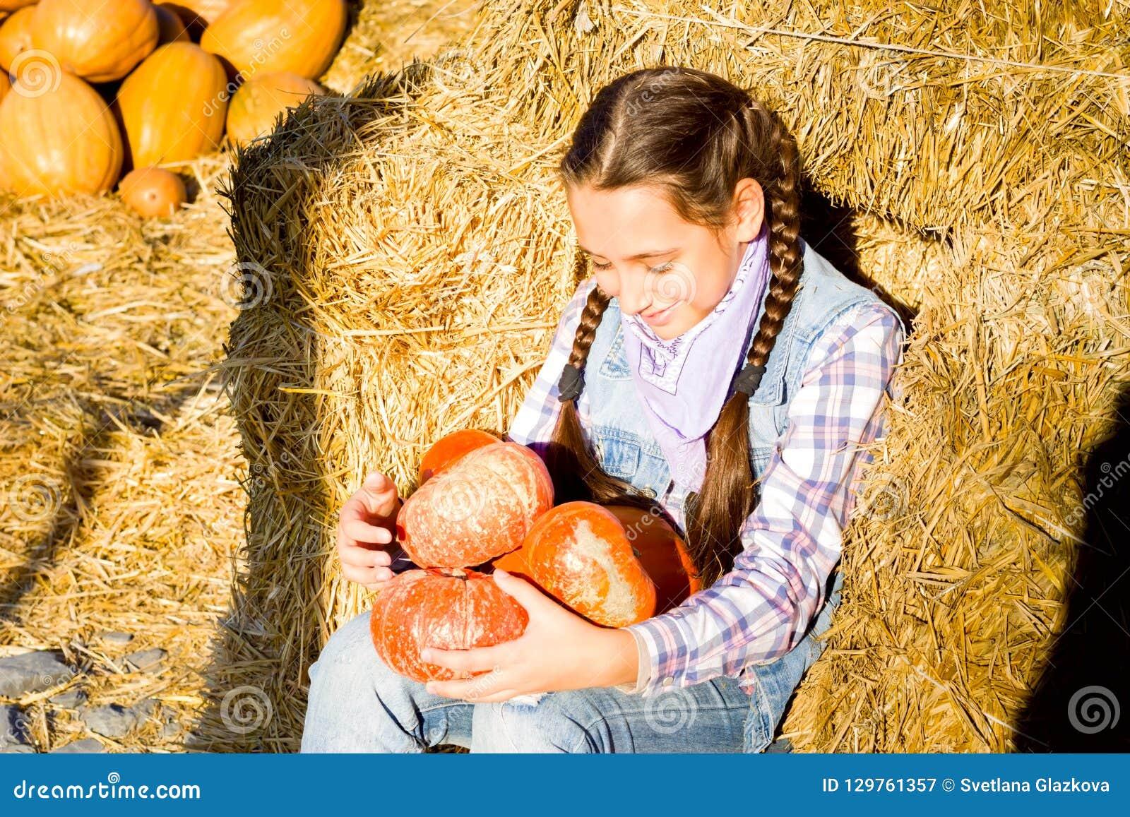Młody nastolatek dziewczyny obsiadanie na słomie z pumkins na gospodarstwo rolne rynku Rodzinny odświętności dziękczynienie, Hall
