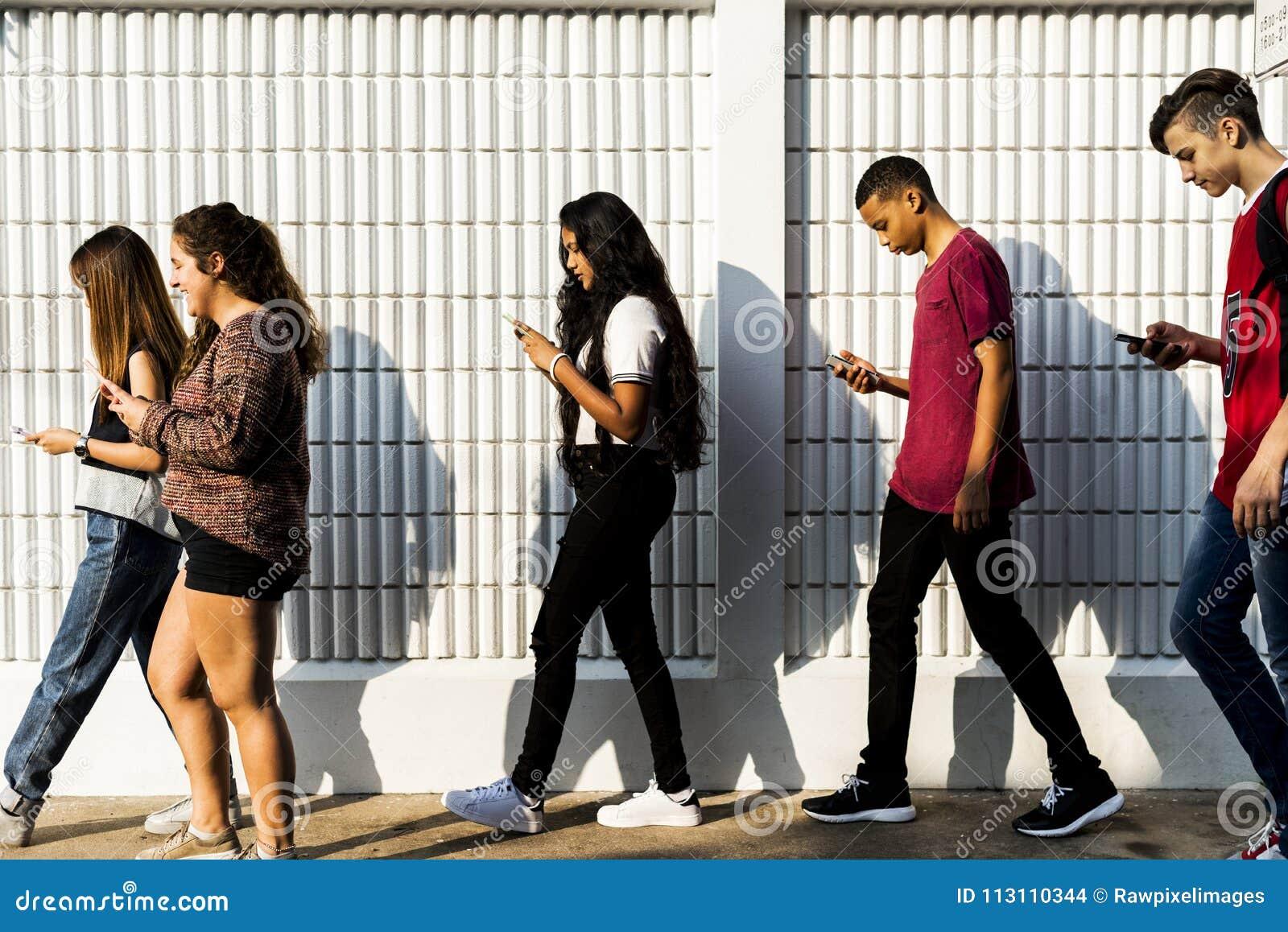 Młody nastolatek patrzeje w ich telefon