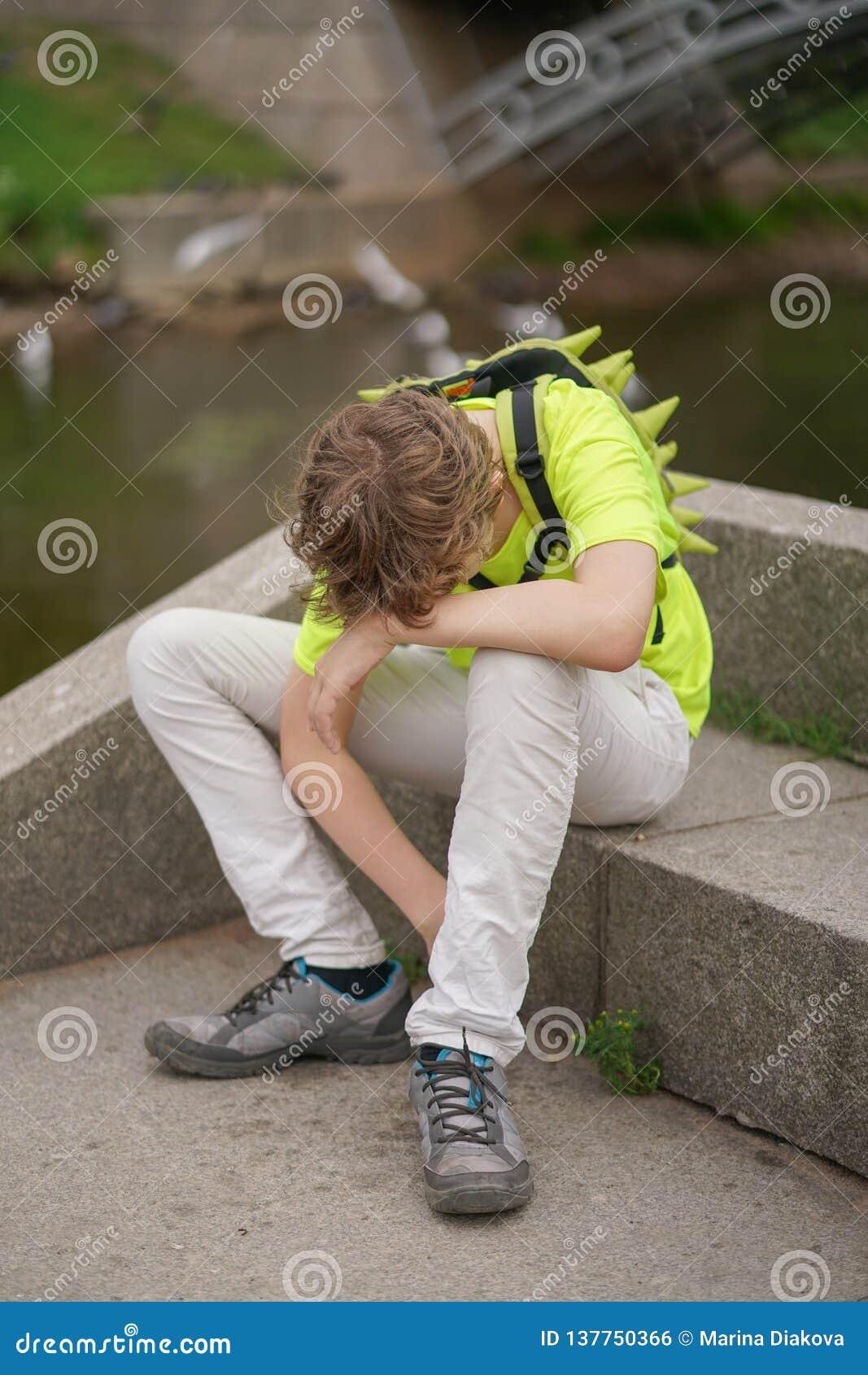Młody nastolatka facet cierpi od migreny utrzymuje jego ręki jego głowa siedzi na naturze winces niewygoda i,