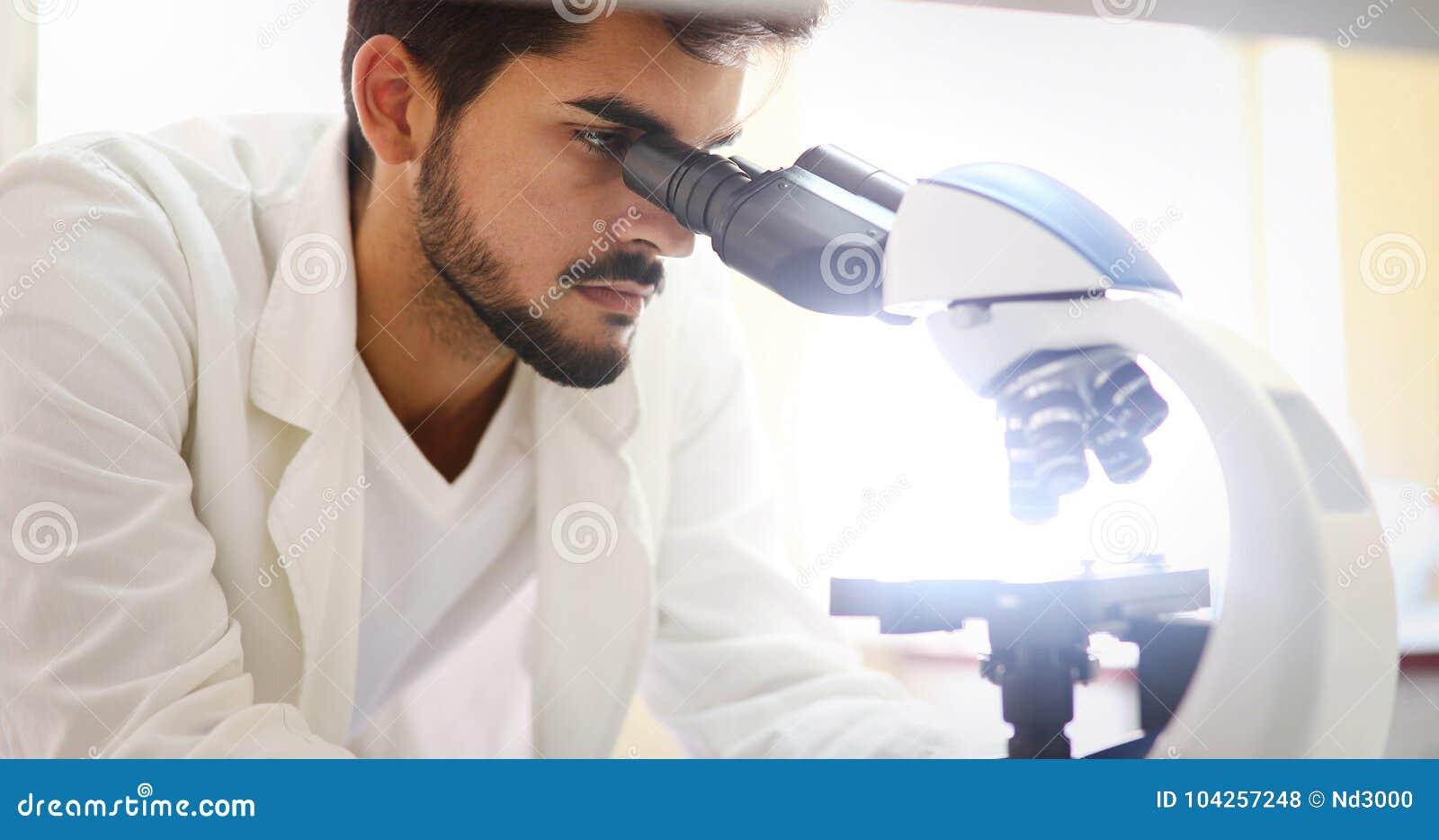 Młody naukowiec patrzeje przez mikroskopu w laboratorium