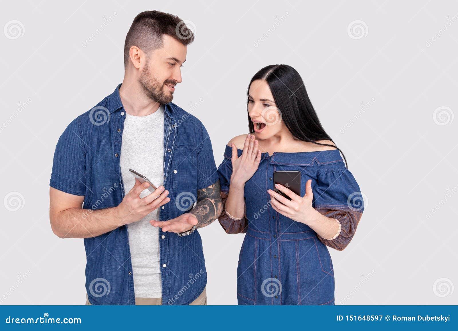 Młody nieogolony mężczyzna w cajgu mienia koszulowym smartphone pokazuje coś na telefonie komórkowym jej żona Zdziwiony młody żeń