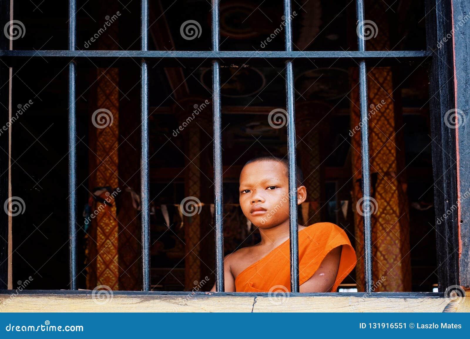 Młody nowicjusza mnicha buddyjskiego zerkanie patrzeje outside okno od jego monasteru