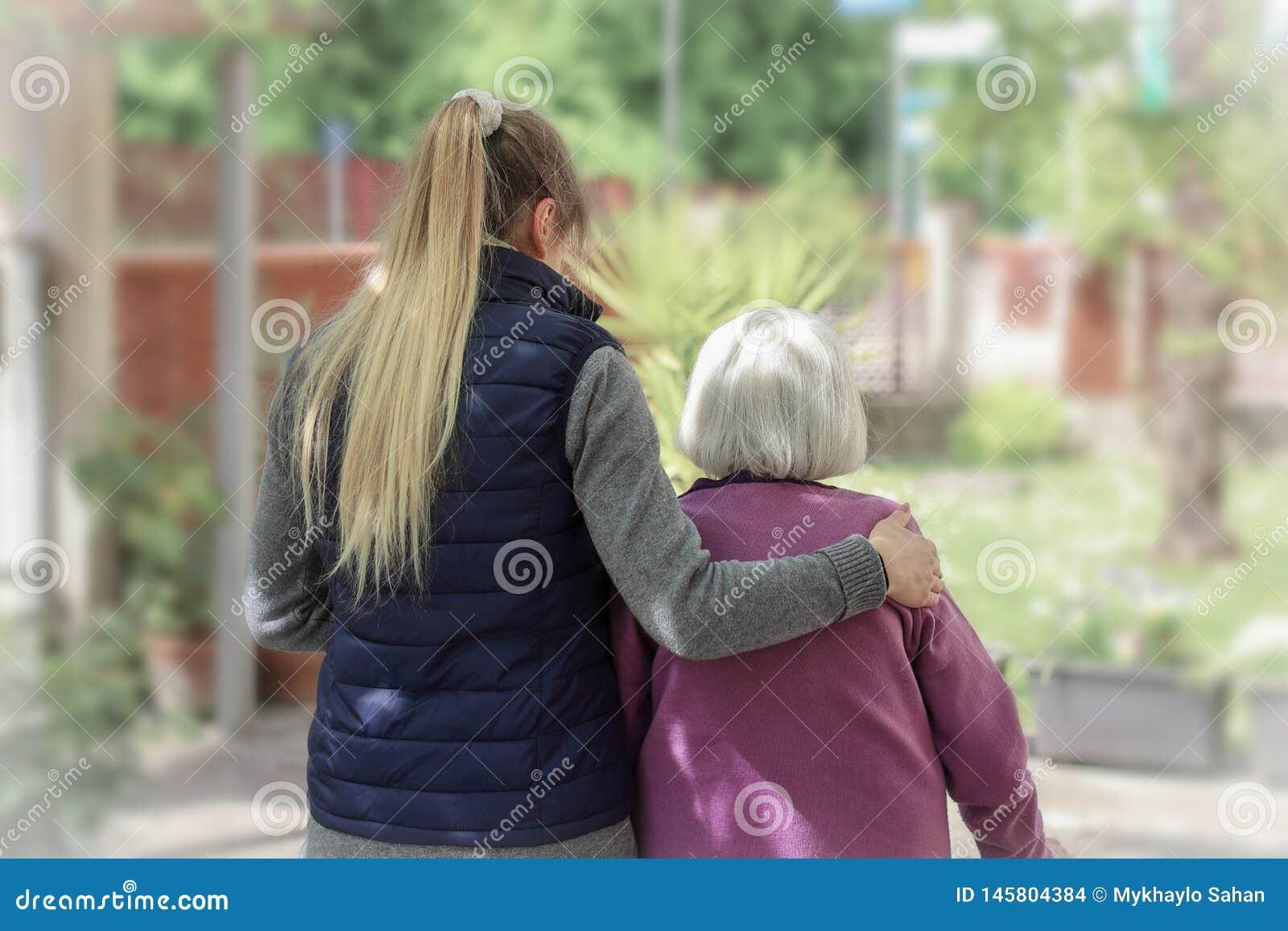 Młody opiekunu odprowadzenie z starszą kobietą w ogródzie z lekkim tłem