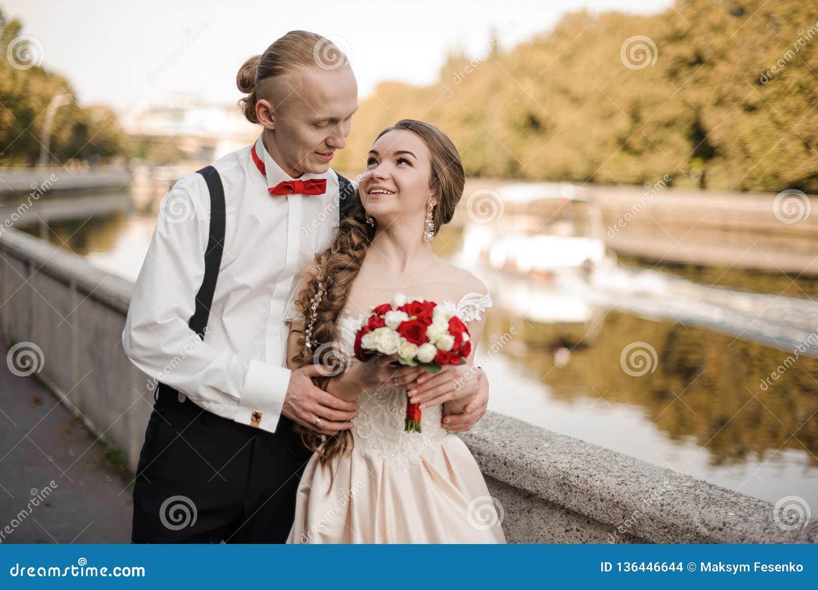 Młody pary małżeńskiej odprowadzenie wzdłuż brzeg rzekiego