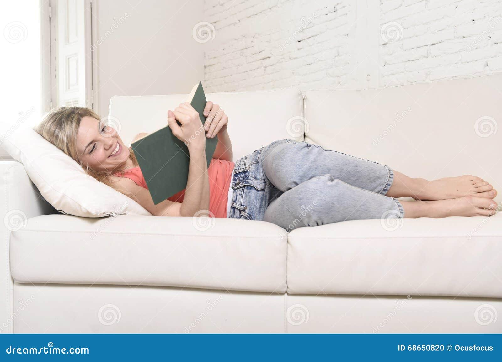 Młody piękny caucasian kobiety czytelniczej książki studiowania kłamać wygodny na domowej kanapie patrzeje szczęśliwy