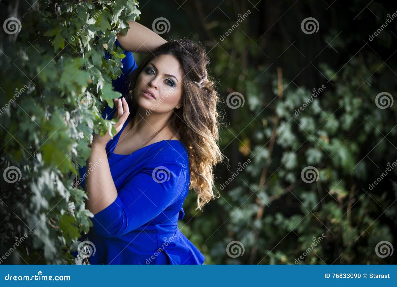 Młody piękny caucasian plus rozmiaru model w błękit sukni outdoors, xxl kobieta na naturze