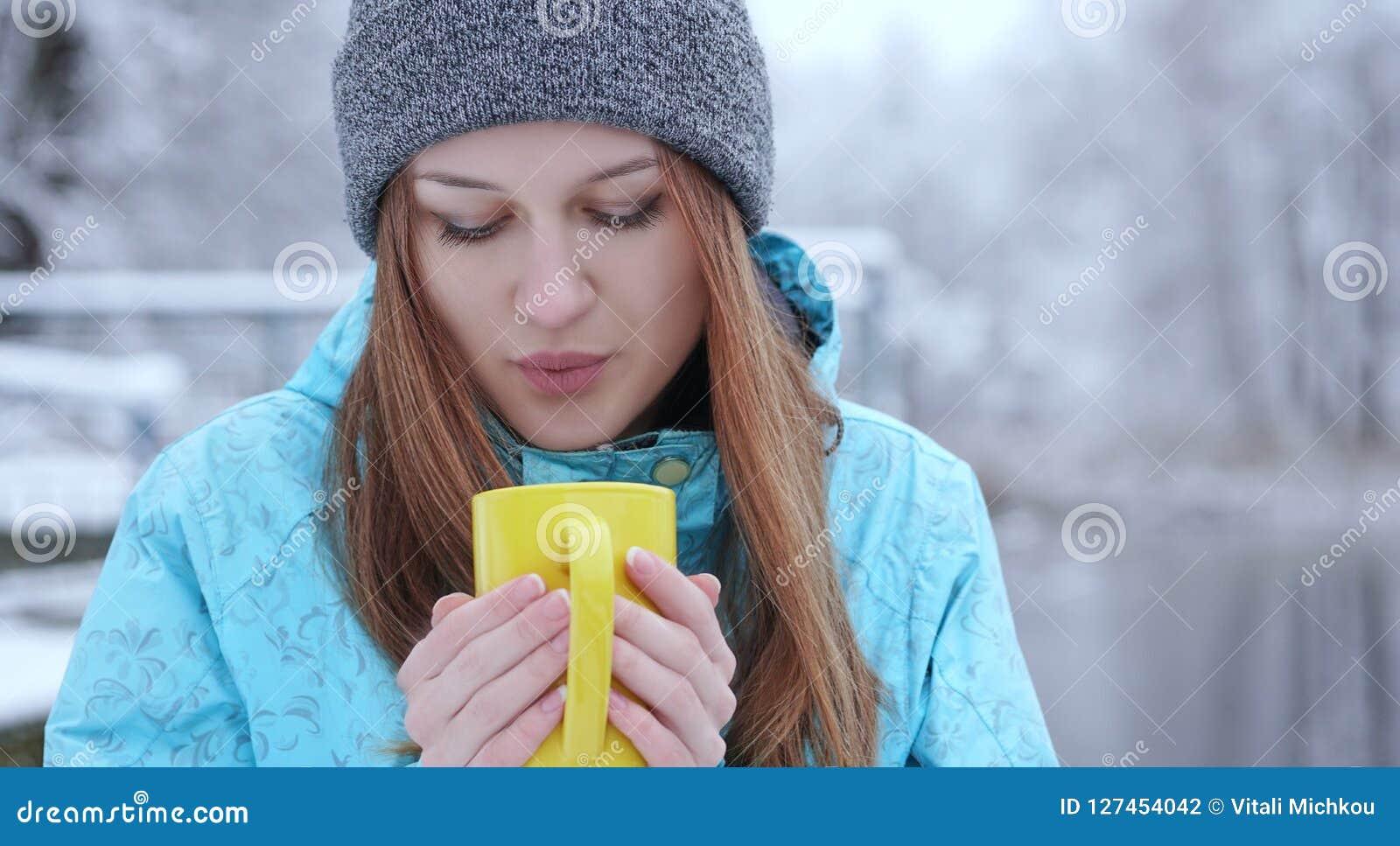Młody piękny dziewczyny dmuchanie na gorącej herbaty lub kawy pozyci na brzeg zimy jezioro