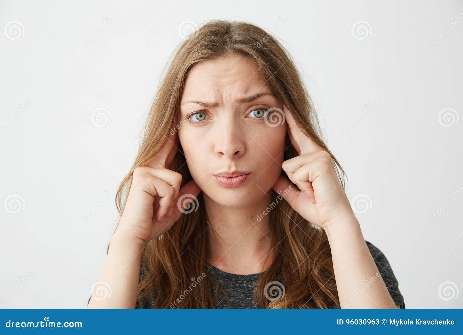 Młody piękny dziewczyny główkowanie z palcami na świątyniach patrzeje kamerę nad białym tłem