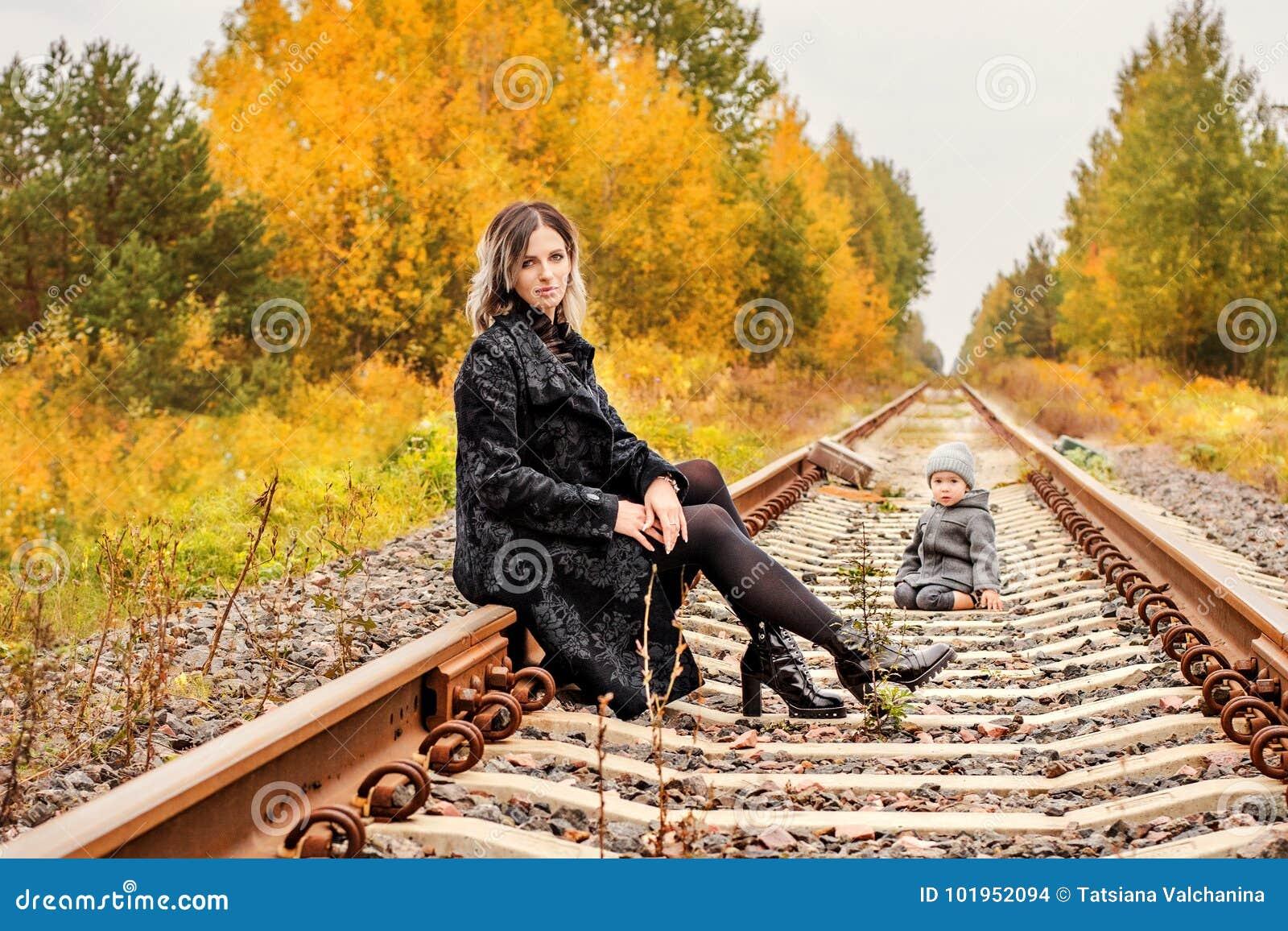 Młody piękny kobiety obsiadanie na śladach w drewnach z walizkami na tle i chłopiec